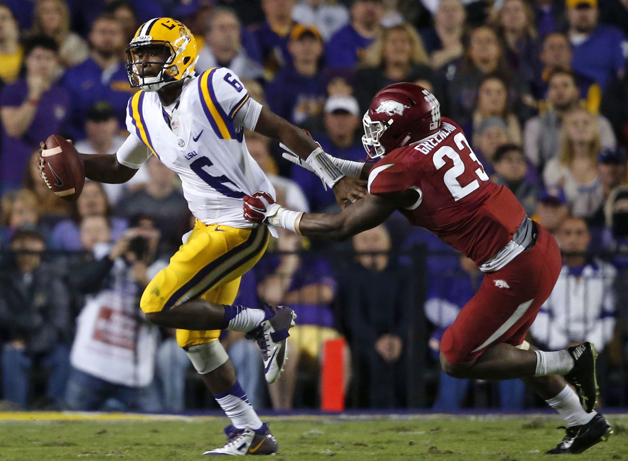LSU quarterback Brandon Harris (6) scrambles to avoid Arkansas linebacker Dre Greenlaw (23) in the first half of an NCAA college football game in Baton Rouge, La., Saturday, Nov. 14, 2015. Harris fumbled on the play setting up an Arkansas touchdown.  (AP