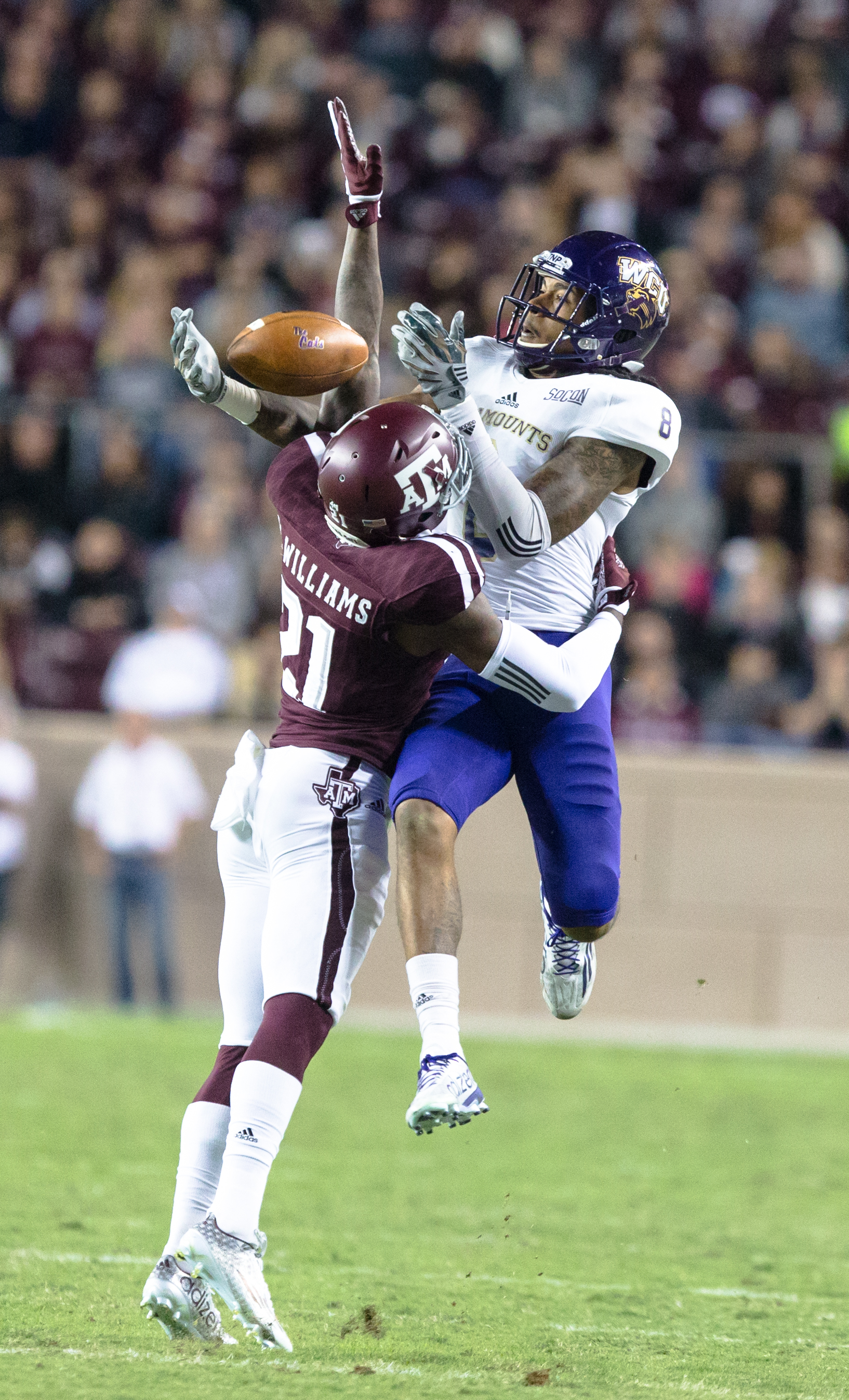 Western Carolina's Spearman Robinson (8) leaps over Texas A&M's Brandon Williams (21) to make the catch during the first half of an NCAA college football game Saturday, Nov. 14, 2015, in College Station, Texas. (AP Photo/Juan DeLeon)