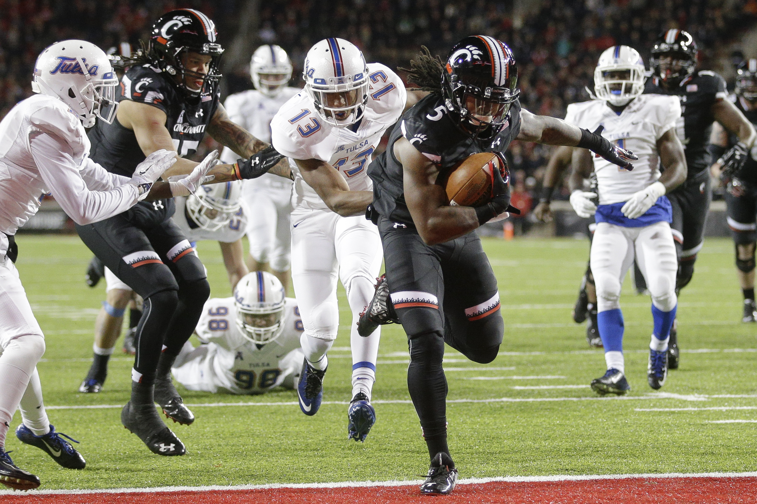Cincinnati running back Mike Boone (5) scores a touchdown on a run against Tulsa safety Jordan Mitchell (13) the first half of an NCAA college football game, Saturday, Nov. 14, 2015, in Cincinnati. (AP Photo/John Minchillo)