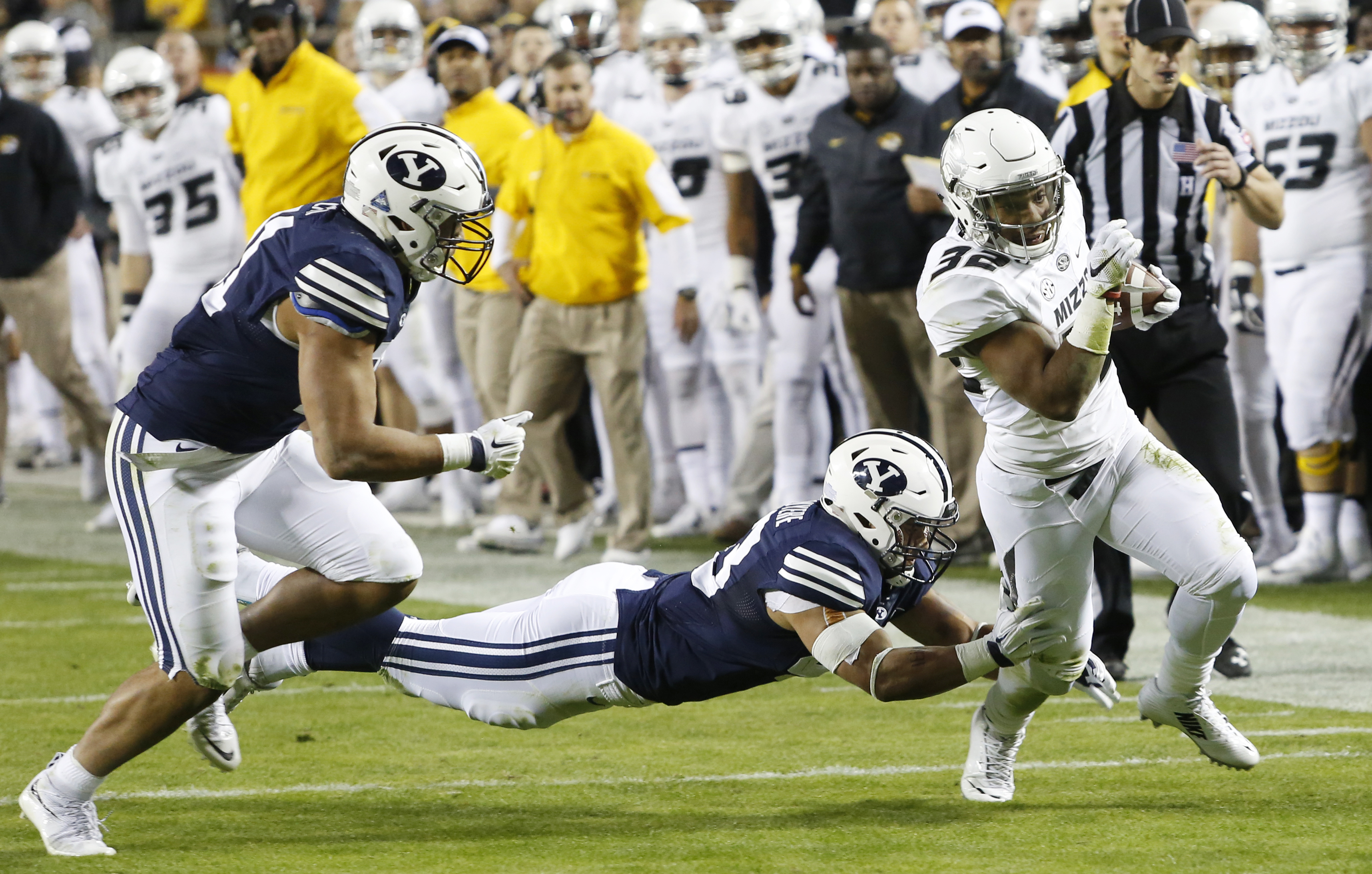 Missouri running back Russell Hansbrough, right, slips past BYU linebackers Jherremya Leuta-Douyere, center, and Harvey Langi, left, in the first half of a college football game at Arrowhead Stadium, Saturday, Nov. 14, 2015, in Kansas City, Mo. (AP Photo/