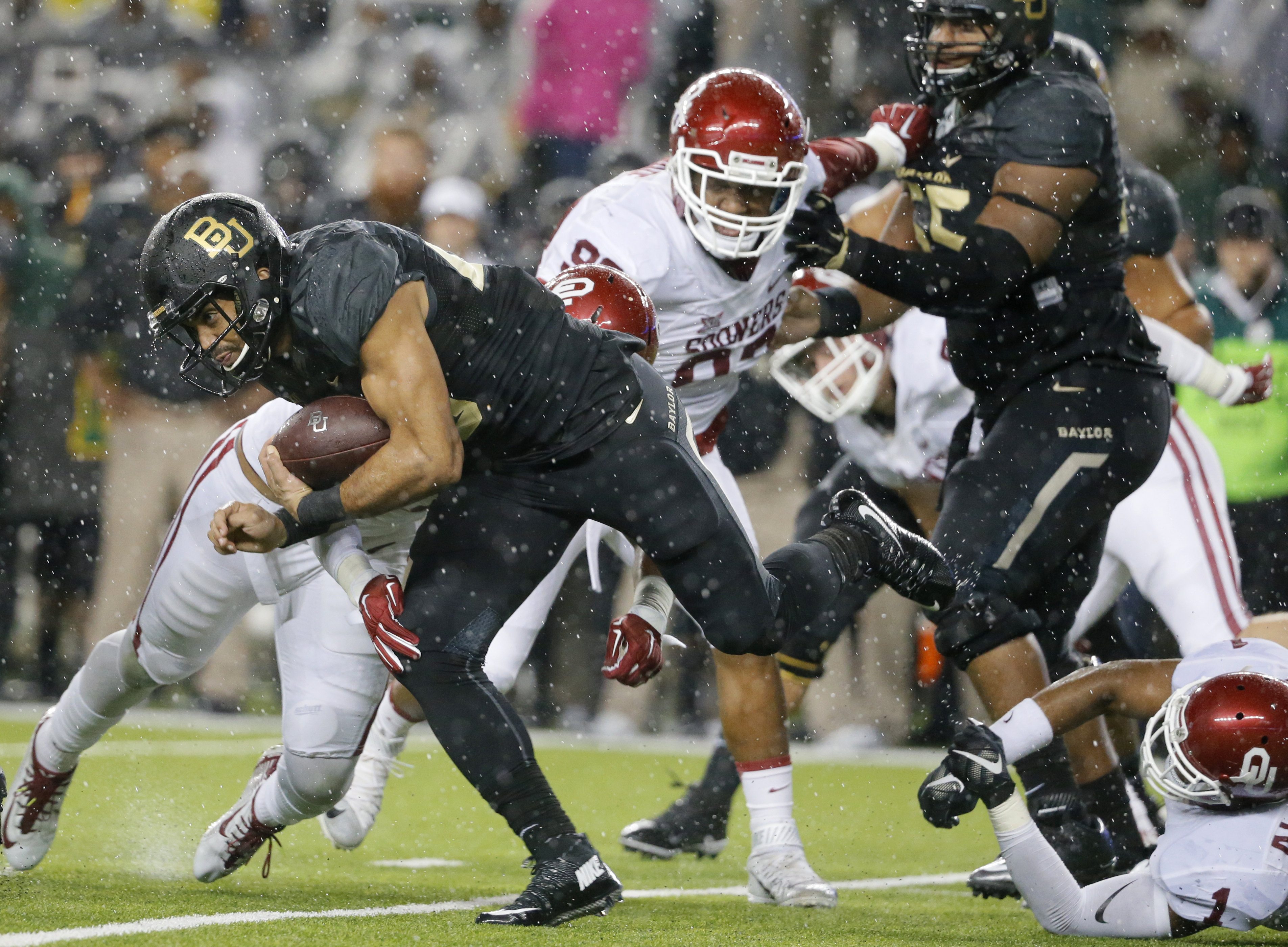 Baylor running back Devin Chafin breaks through Oklahoma tackles as he gains yardage on a running play in the first half of an NCAA college football game Saturday, Nov. 14, 2015, in Waco, Texas. (AP Photo/Tony Gutierrez)
