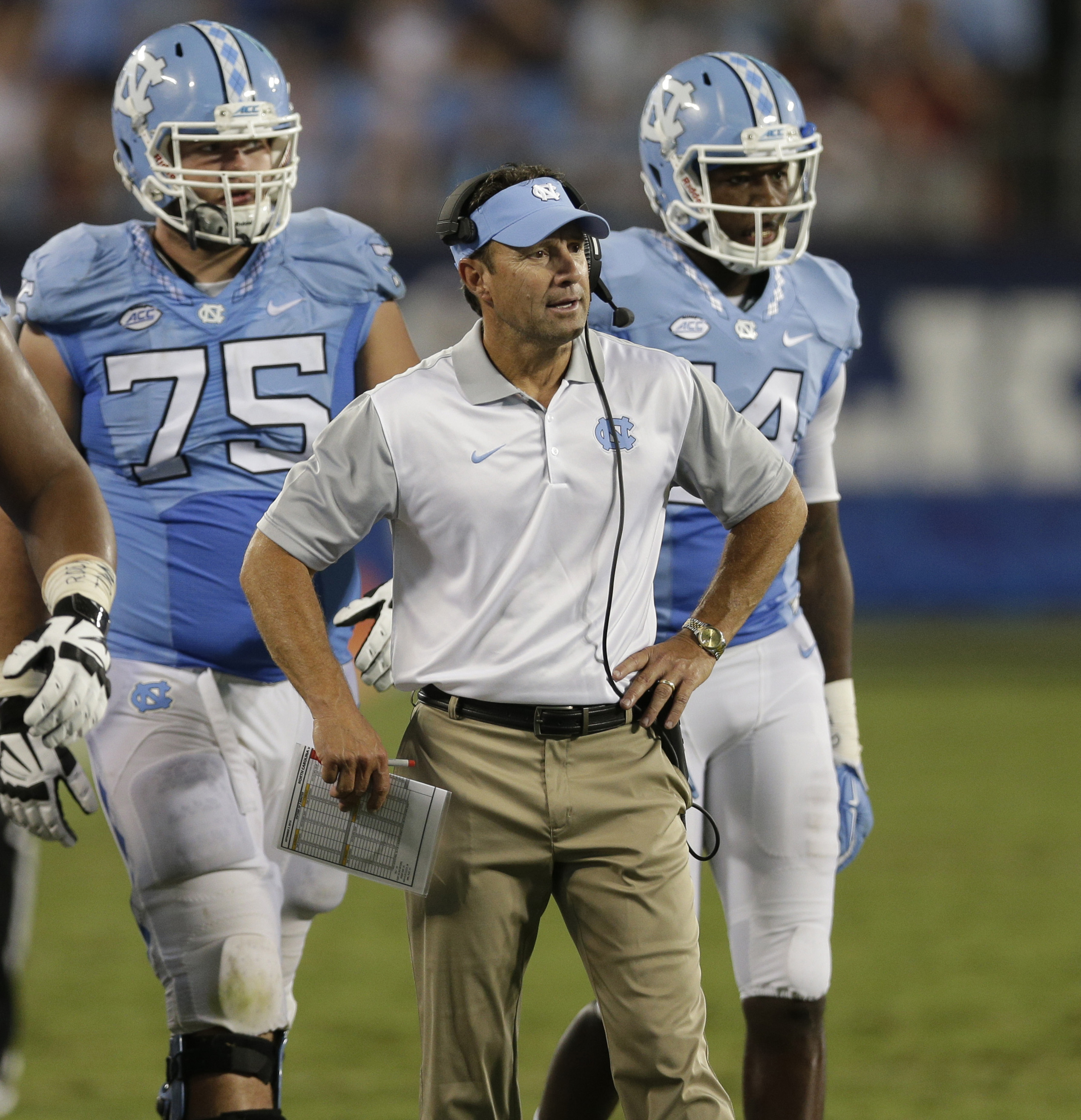 FILE - In this Sept. 3, 2015, file photo, North Carolina head coach Larry Fedora talks to his team during a timeout in the second half of an NCAA college football game against South Carolina in Charlotte, N.C. North Carolina's offense is rolling to big ya