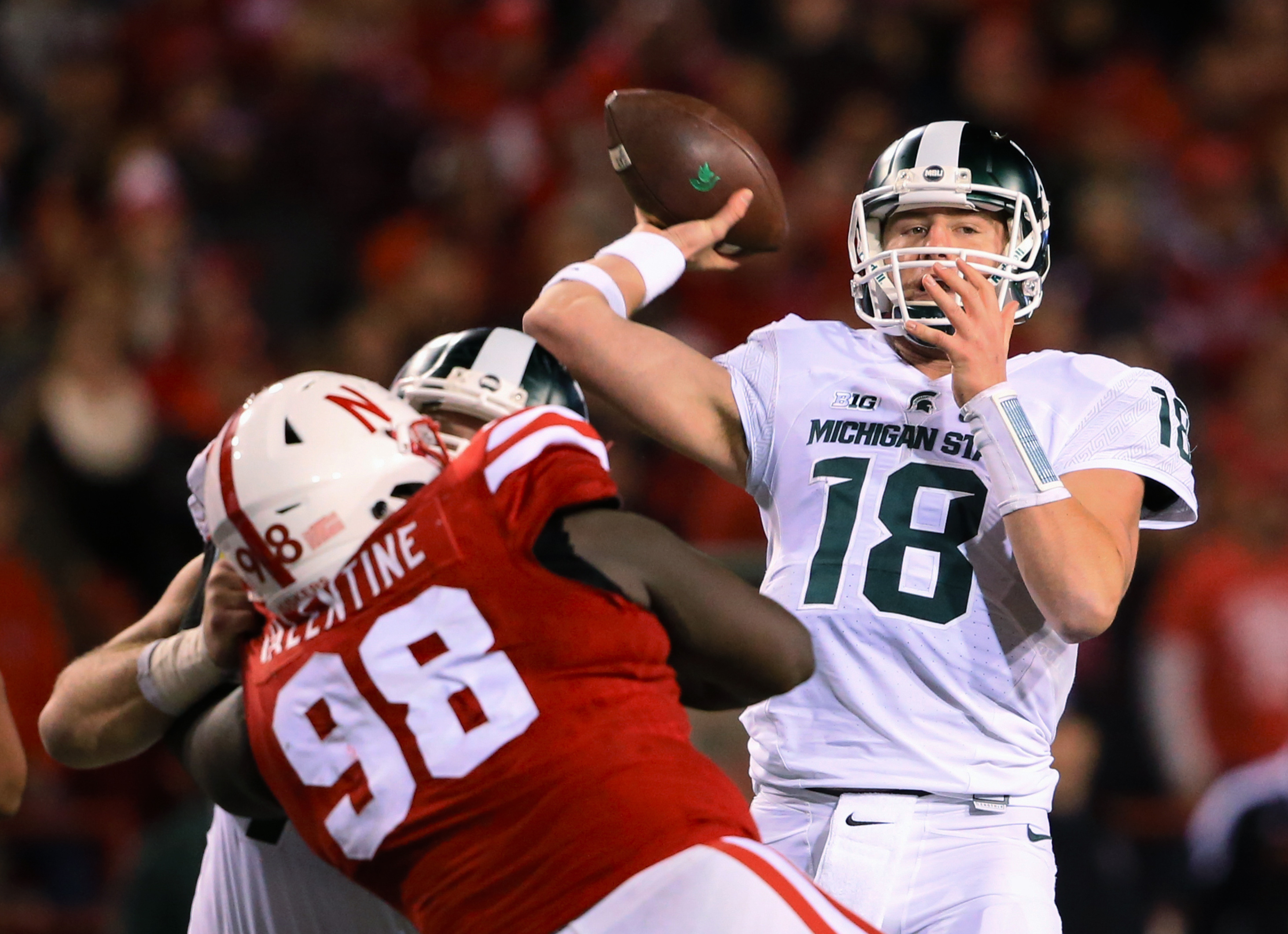 FILE - In this Nov. 7, 2015, file photo, Michigan State quarterback Connor Cook (18) throws during the team's NCAA college football game against Nebraska in Lincoln, Neb. Cook missed much of last week's game after taking a shot to his throwing shoulder. H