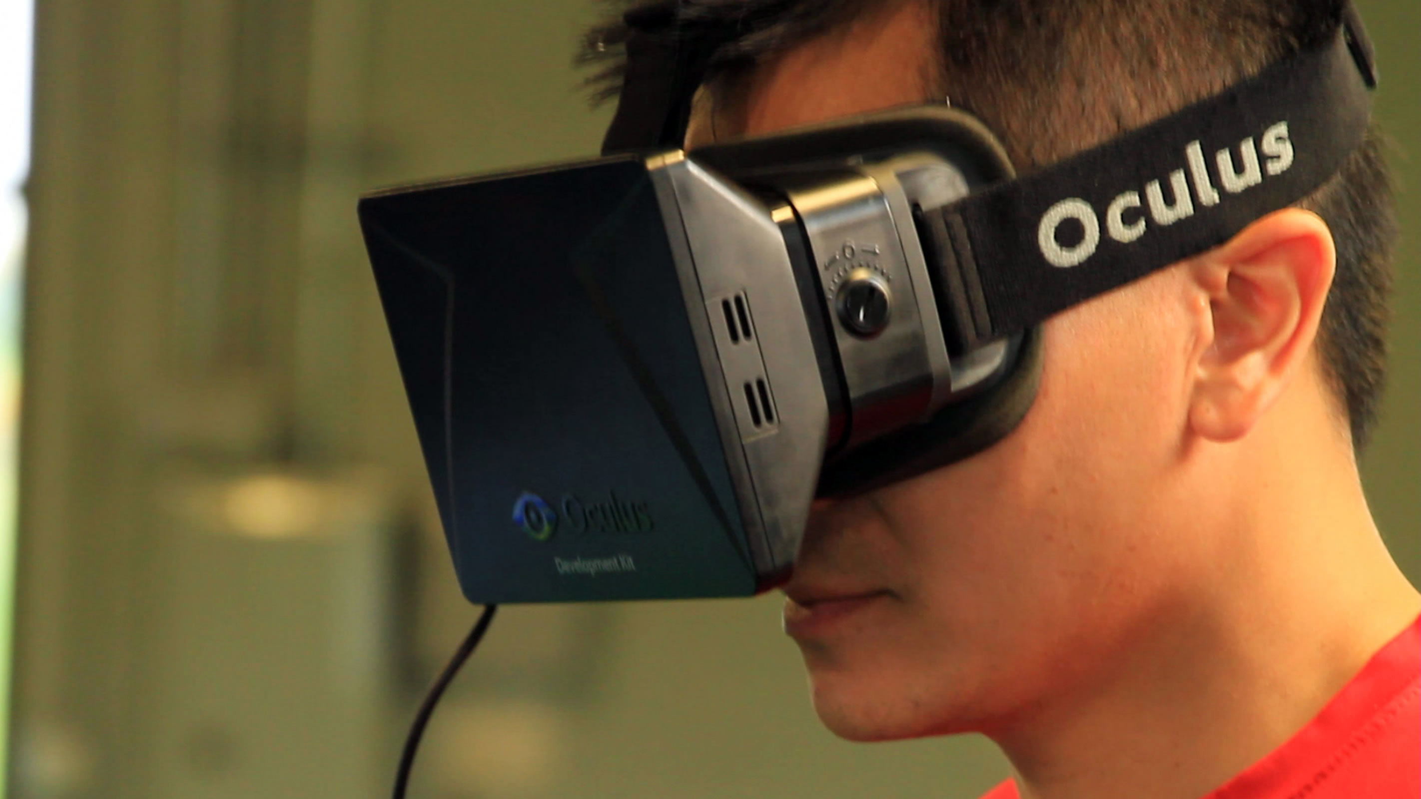 In this Aug. 11, 2014,  photo provided by EON Sports VR, sports performance manager and strength and conditioning coach Doran Lovan wears a vitual reality headset to view a 360-degree virtual simulation, in Overland, Kansas. College football teams have be