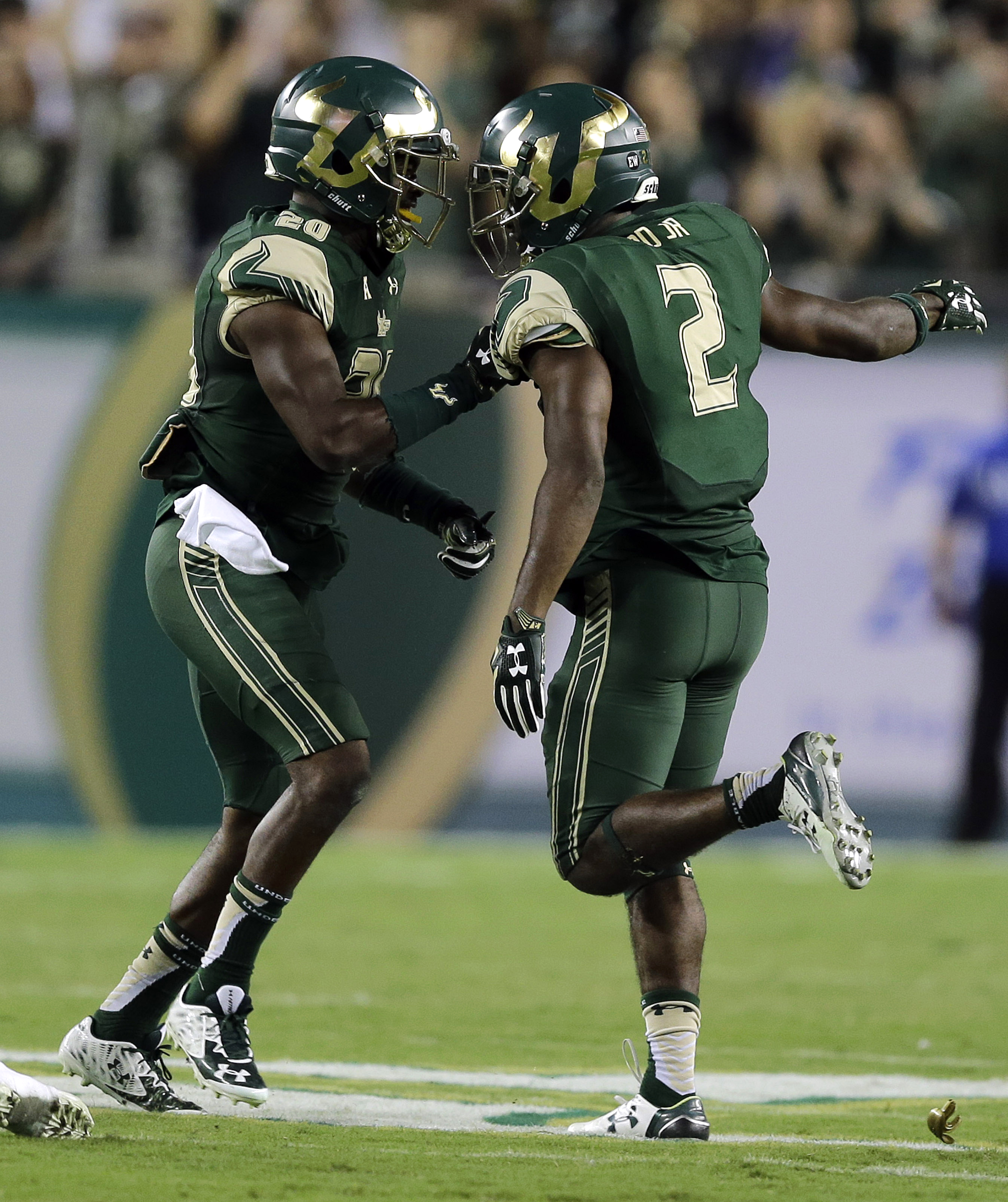 South Florida defensive back Jamie Byrd (2) celebrates with teammate Devin Abraham (20) after intercepting a pass by Cincinnati quarterback Gunner Kiel during the first quarter of an NCAA college football game Friday, Nov. 20, 2015, in Tampa, Fla. (AP Pho