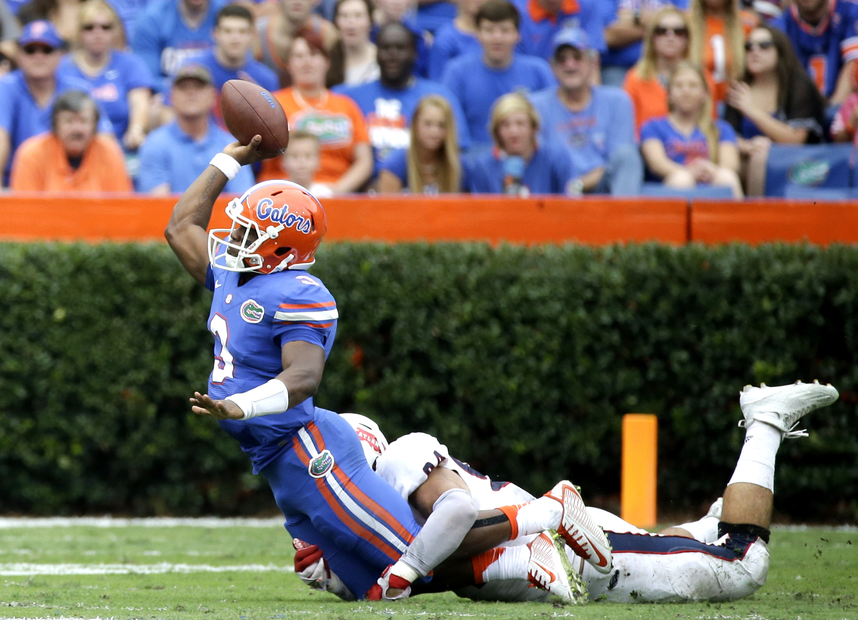 Florida quarterback Treon Harris (3) tires to throws a pass as he is tackled by Florida Atlantic defensive lineman Hunter Snyder, right, during the first half of an NCAA college football game, Saturday, Nov. 21, 2015, in Gainesville, Fla. Harris was ruled