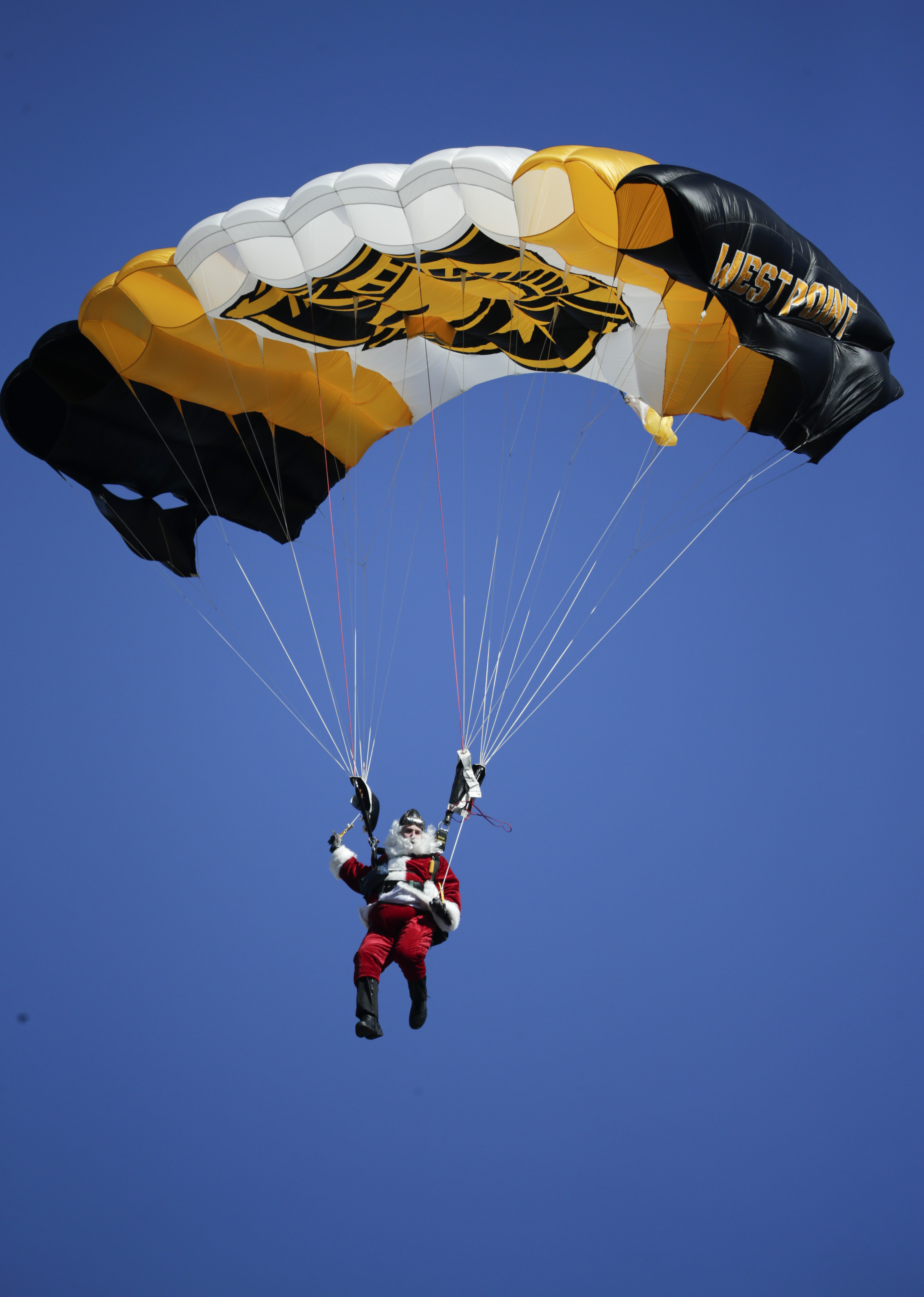 Cadet Jordan Komm, of Houston, dressed as Santa Claus, parachutes into Michie Stadium before an NCAA college football game between Army and Rutgers on Saturday, Nov. 21, 2015, in West Point, N.Y. (AP Photo/Mike Groll)