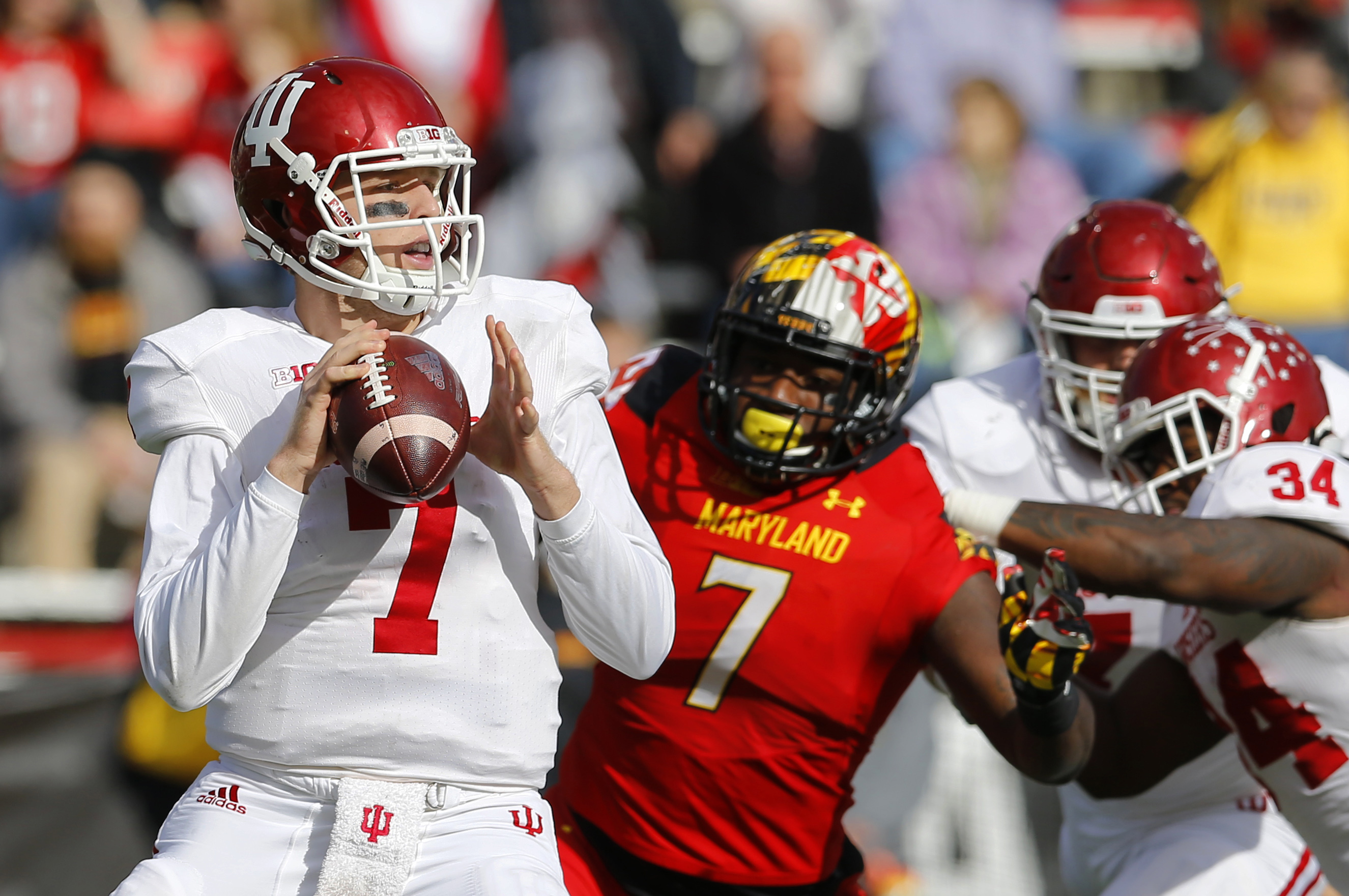 Indiana quarterback Nate Sudfeld, left, looks for a receiver as he is pressured by Maryland defensive lineman Yannick Ngakoue (7) in the first half of an NCAA college football game, Saturday, Nov. 21, 2015, in College Park, Md. (AP Photo/Patrick Semansky)