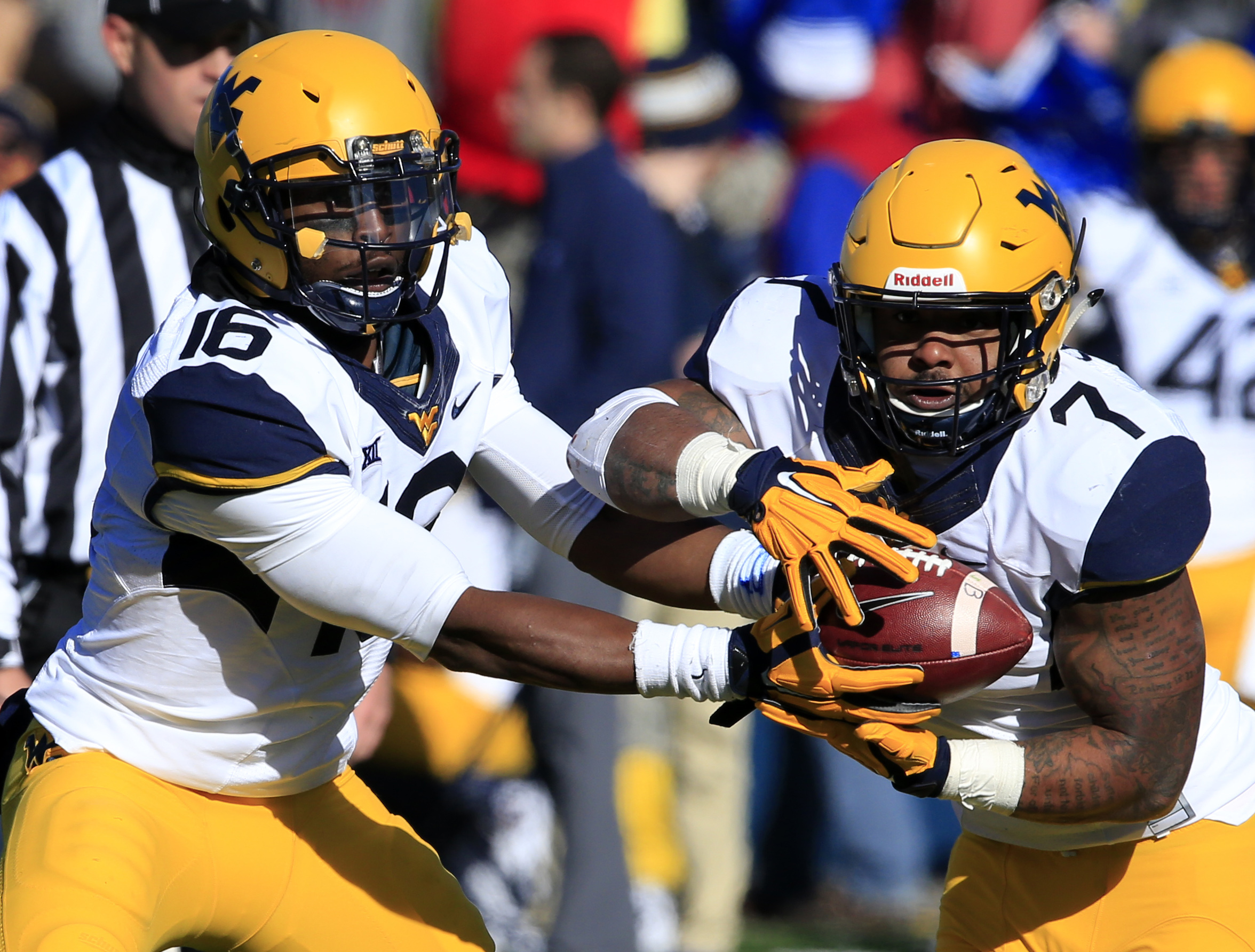 West Virginia quarterback William Crest Jr. (16) hands off to running back Andrew Buie (7) during the second half of an NCAA college football game against Kansas in Lawrence, Kan., Saturday, Nov. 21, 2015. (AP Photo/Orlin Wagner)