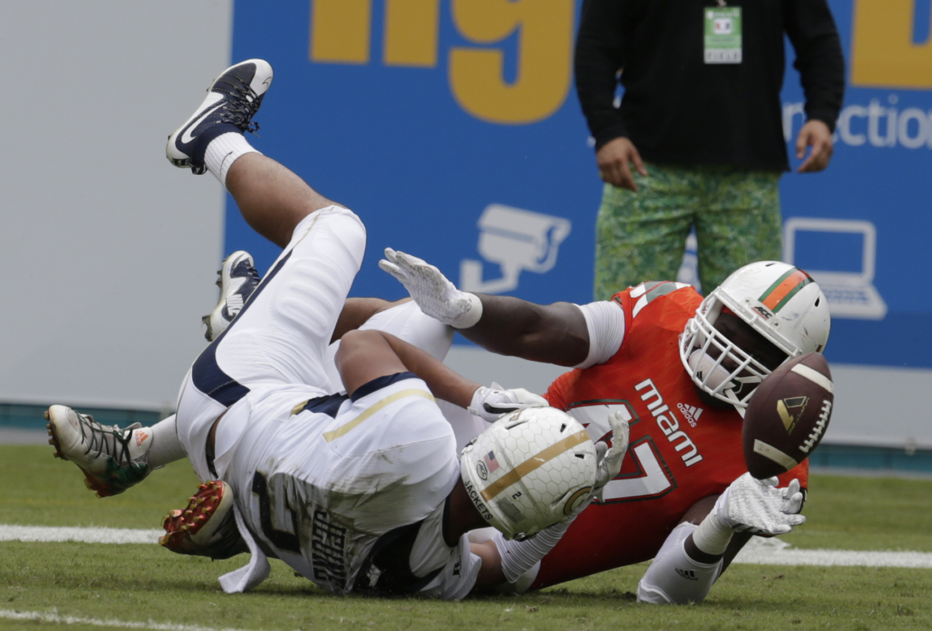 Miami defensive lineman Ufomba Kamalu (47) fumbles the ball he is brought down by Georgia Tech wide receiver Ricky Jeune after recovering a Georgia Tech fumble in the first half of an NCAA college football game, Saturday, Nov. 21, 2015 in Miami Gardens, F