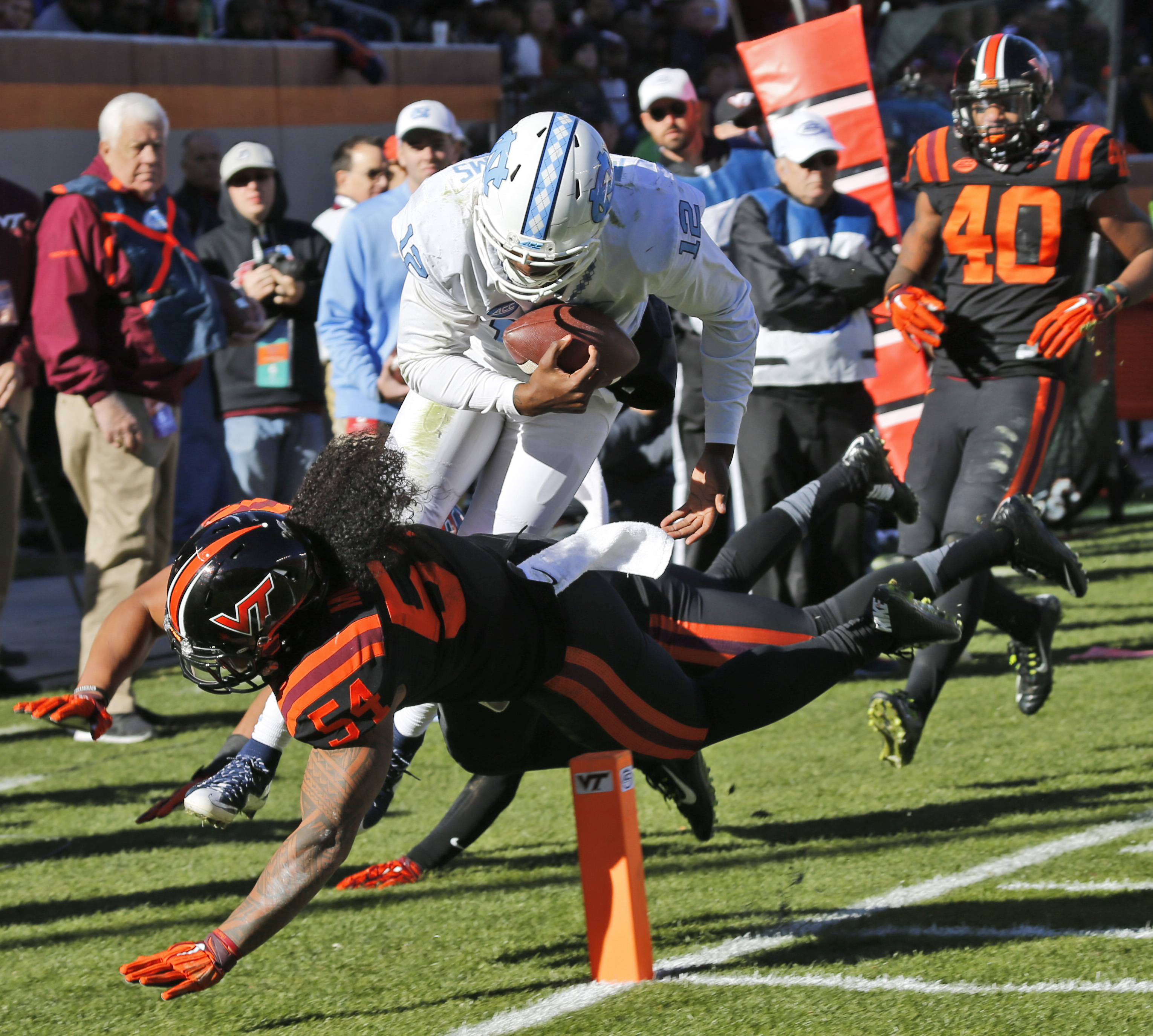 North Carolina quarterback Marquise Williams (12) dives toward the end zone as Virginia Tech linebacker Andrew Motuapuaka (54) defends during the second half of an NCAA college football game in Blacksburg, Va., Saturday, Nov. 21, 2015.  Williams was short