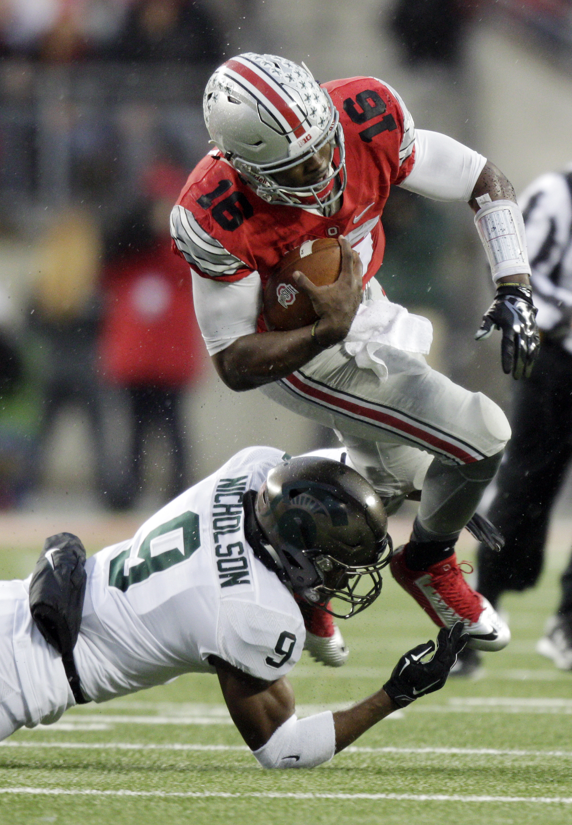 Michigan State safety Montae Nicholson, left, tackles Ohio State running back Ezekiel Elliott during the first quarter of an NCAA college football game, Saturday, Nov. 21, 2015, in Columbus, Ohio. (AP Photo/Jay LaPrete)