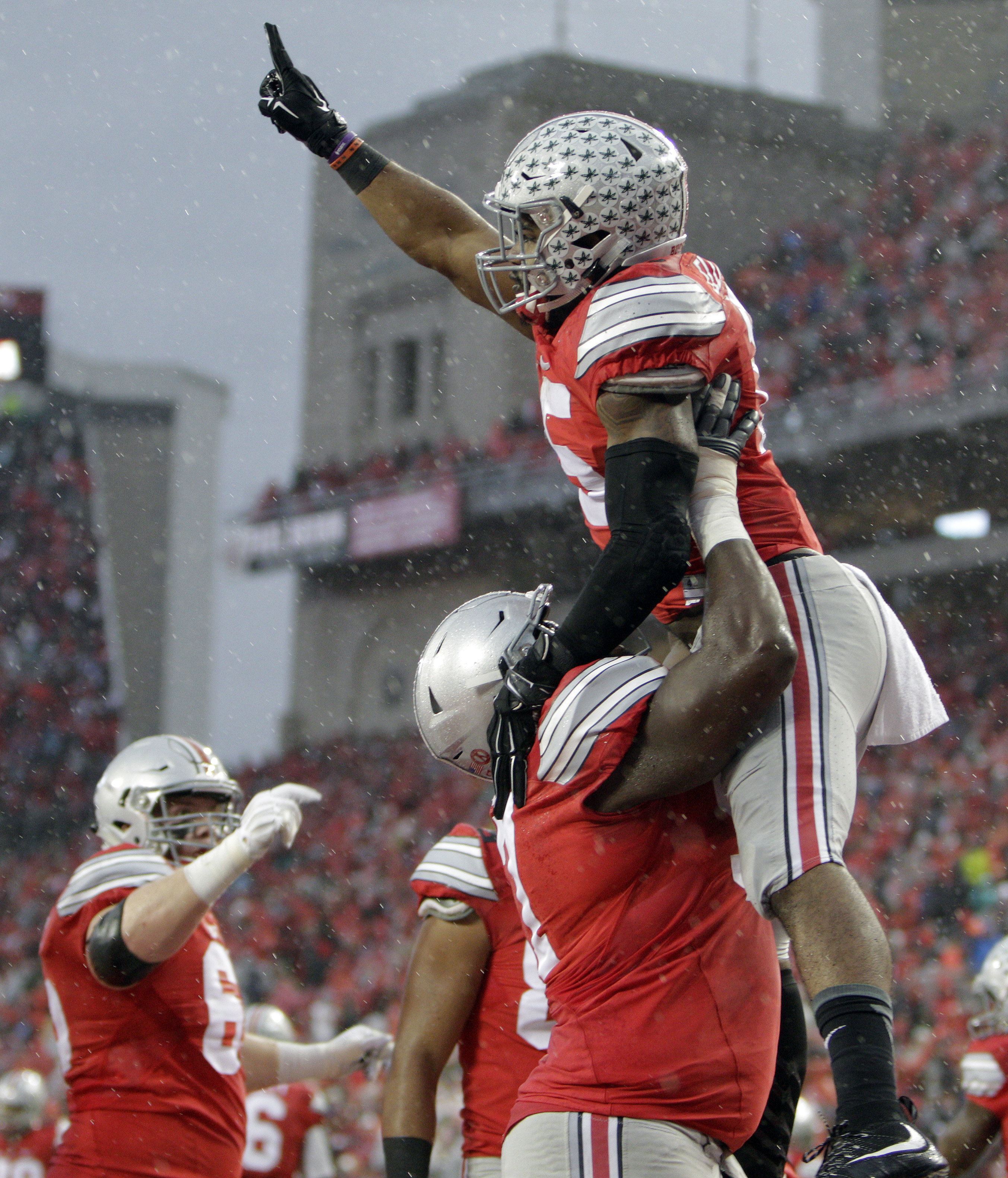 Ohio State running back Ezekiel Elliott , right, celebrates his touchdown against Michigan State with teammate Chase Farris during the second quarter of an NCAA college football game, Saturday, Nov. 21, 2015, in Columbus, Ohio. (AP Photo/Jay LaPrete)