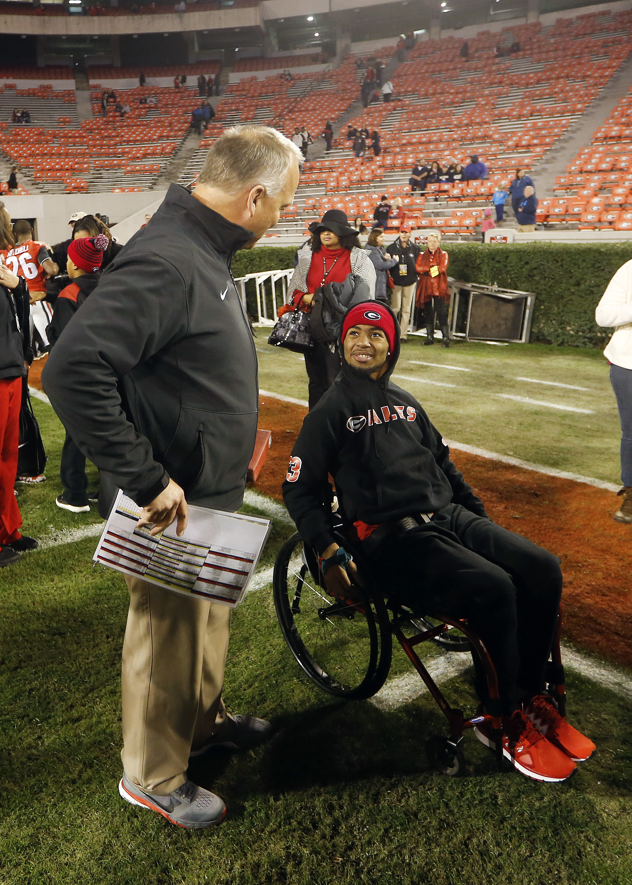 Injured Southern University receiver Devon Gales talks with Georgia head coach Mark Richt before an NCAA college football game between Georgia and Georgia Southern on Saturday, Nov. 21, 2015, in Athens, Ga. Gales was paralyzed Sept. 26, 2015 while blockin