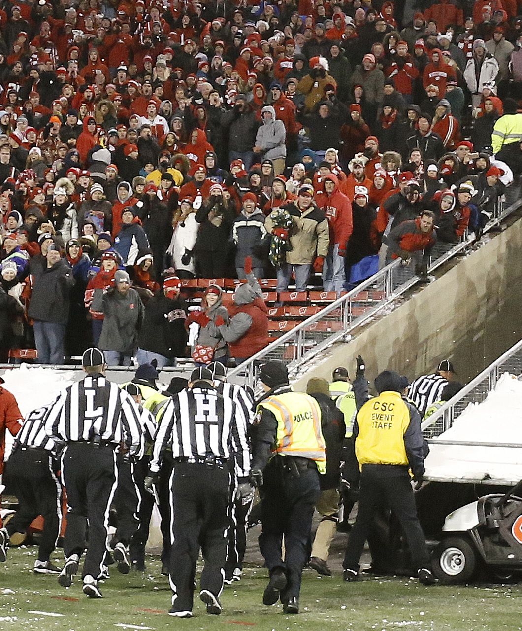 Referees are escorted off the field as fans throw snowballs during the second half of an NCAA college football game between Wisconsin and Northwestern Saturday, Nov. 21, 2015, in Madison, Wis. Northwestern won 13-7. (AP Photo/Morry Gash)