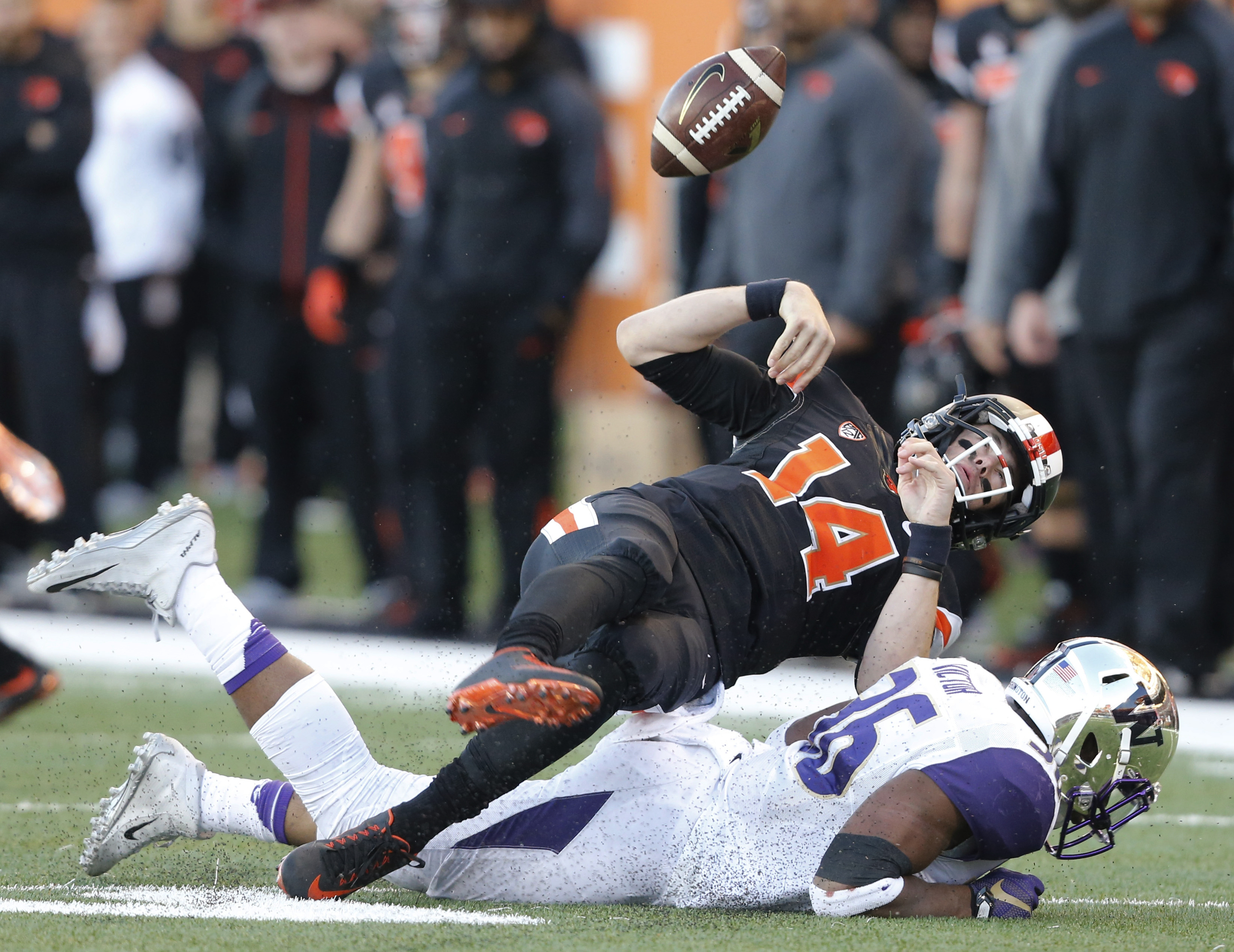 Oregon State quarterback Nick Mitchell fumbles the ball after being hit by Washington's Azeem Victory in the first half of an NCAA football game, in Corvallis, Ore., on Saturday, Nov. 21, 2015. Washington recovered the fumble. y(AP Photo/Timothy J. Gonzal