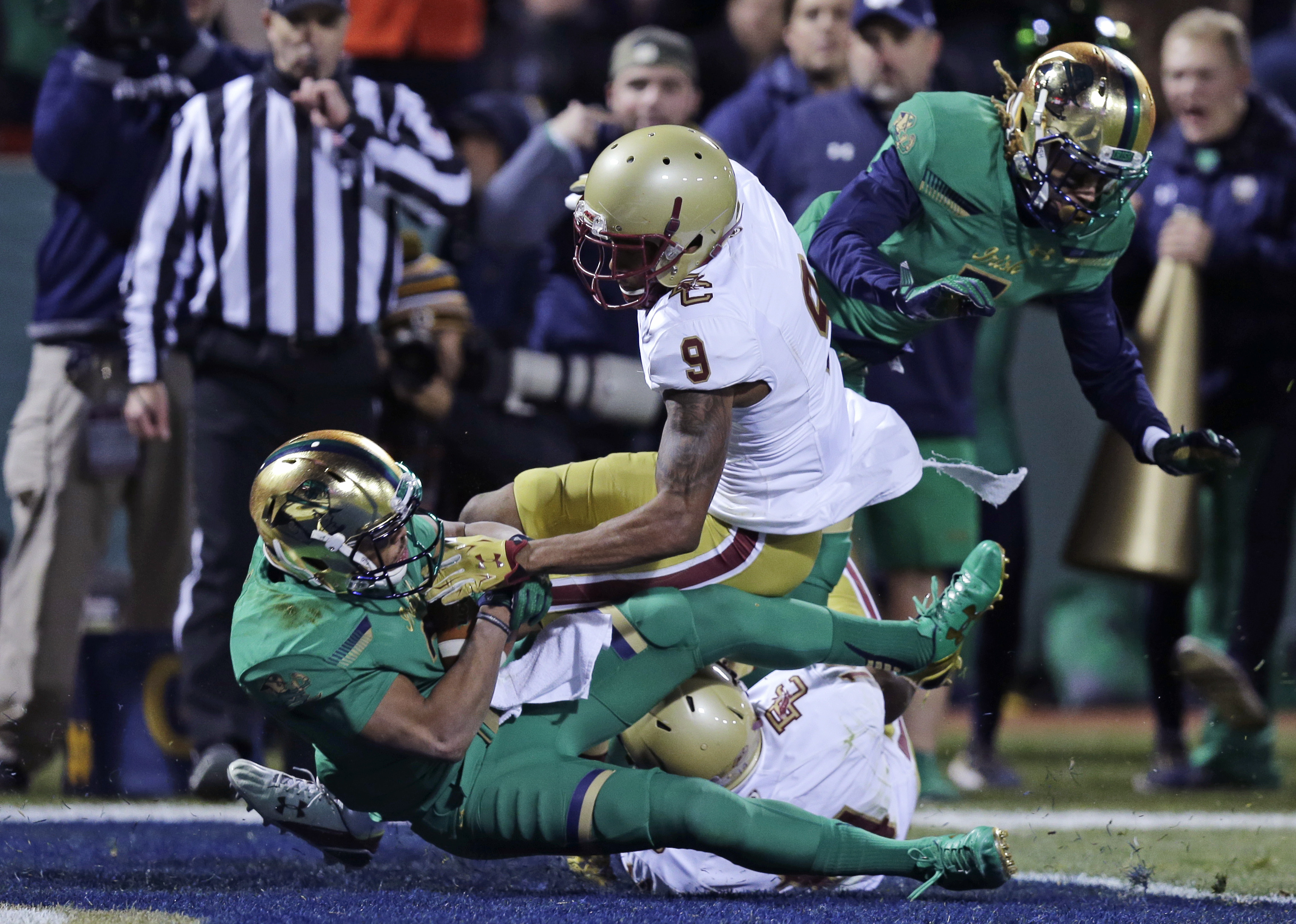 Notre Dame wide receiver Amir Carlisle, left, hangs onto the ball as he drops into the end zone for a touchdown against Boston College defensive backs John Johnson (9) and Gabriel McClary, rear, during the first half of the Shamrock Series NCAA college fo