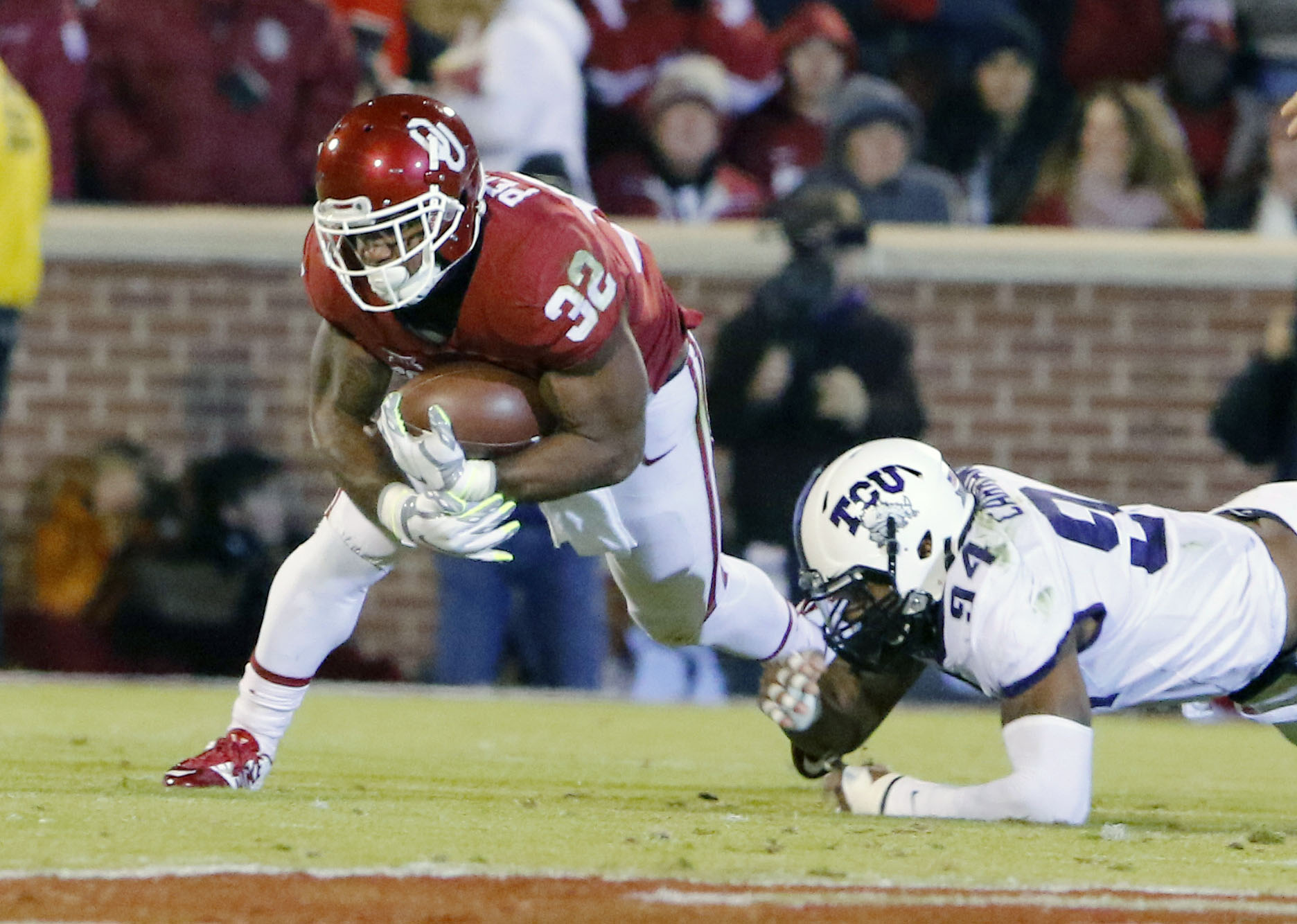 Oklahoma running back Samaje Perine (32) escapes a tackle by TCU defensive end Josh Carraway (94) during the first quarter of an NCAA college football game in Norman, Okla., Saturday, Nov. 21, 2015. (AP Photo/Alonzo Adams)