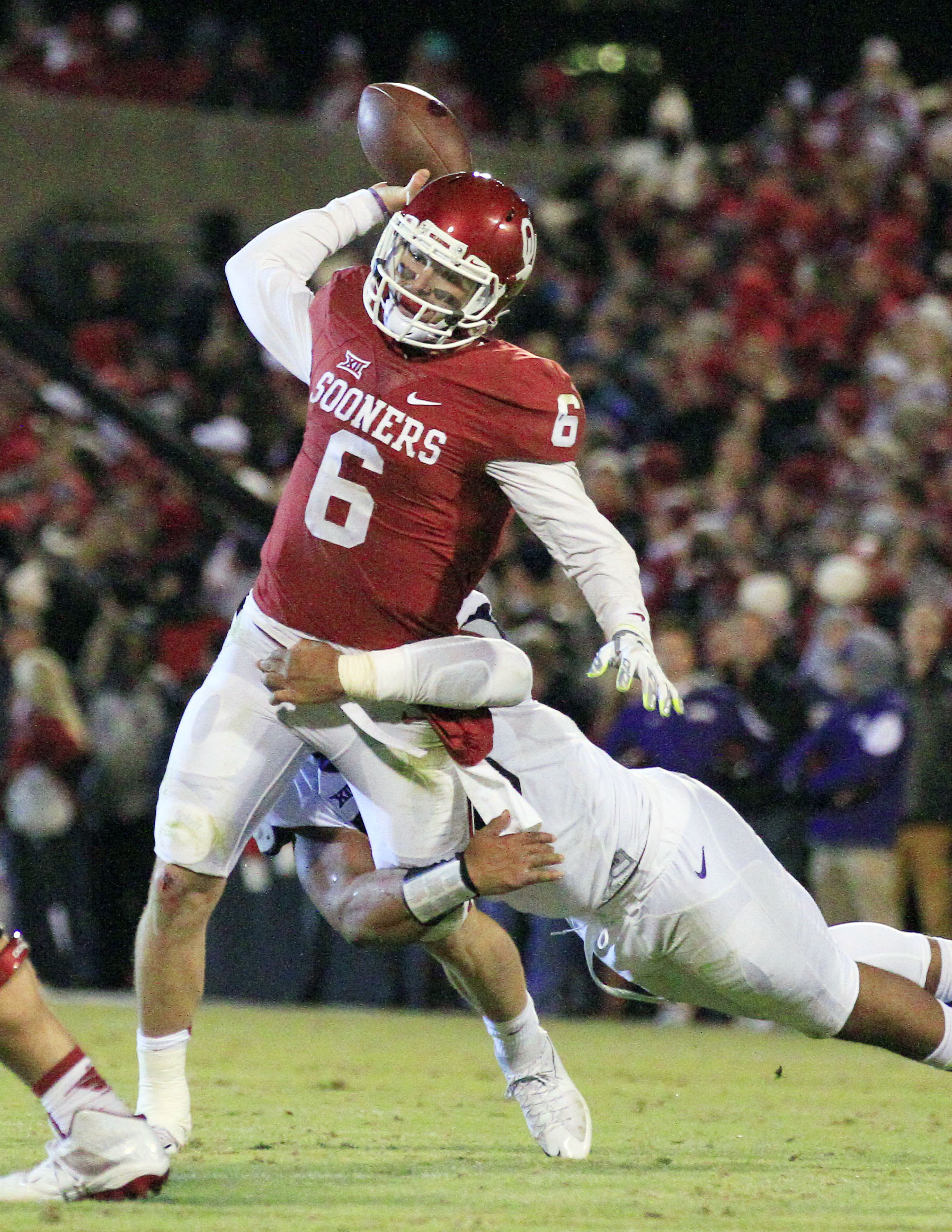 Oklahoma quarterback Baker Mayfield (6) is tackled by TCU defensive tackle Aaron Curry (95) as he passes during the second quarter of an NCAA college football game in Norman, Okla., Saturday, Nov. 21, 2015. (AP Photo/Alonzo Adams)