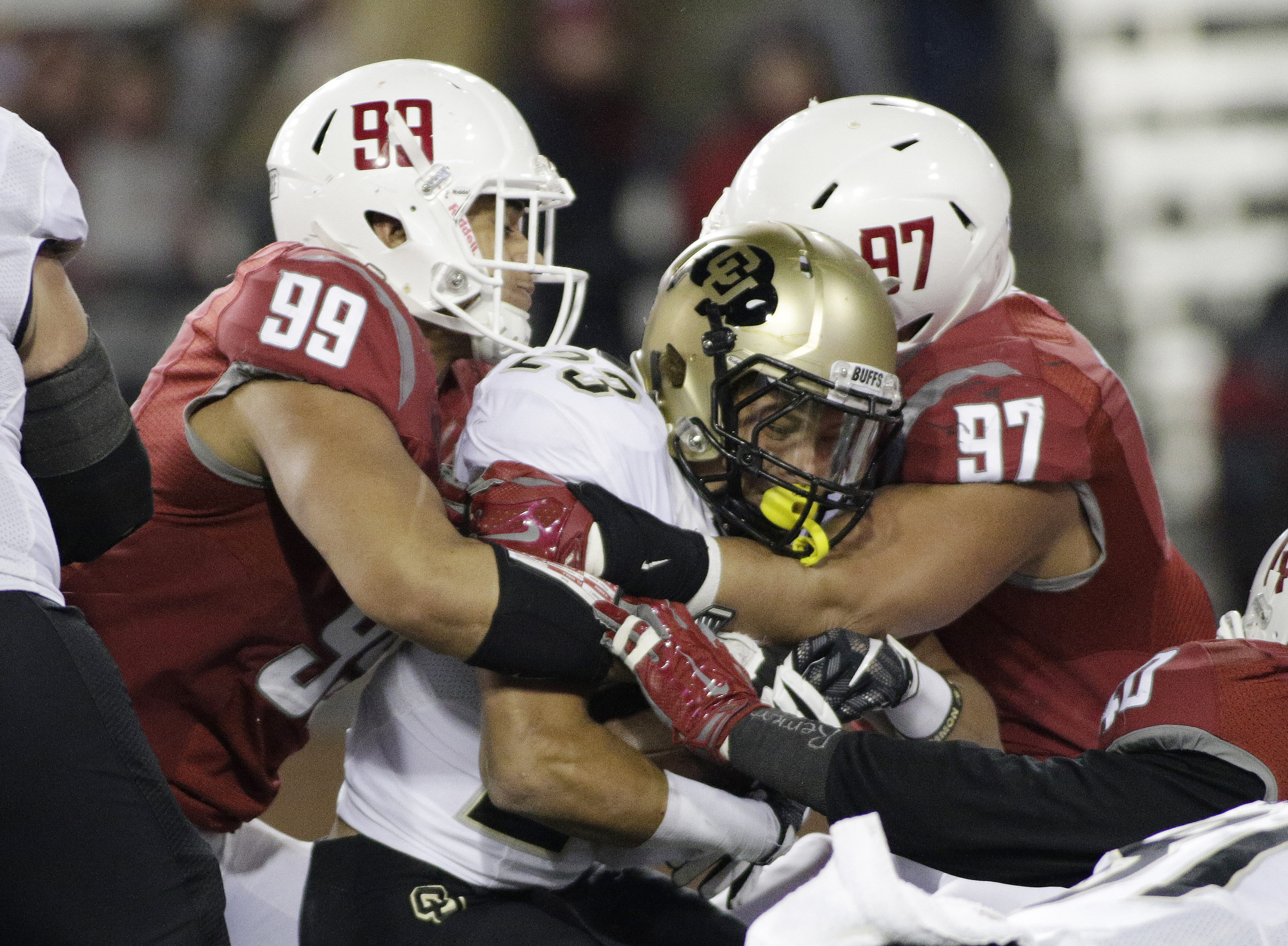 Washington State defensive linemen Darryl Paulo (99) and Destiny Vaeao (97) take down Colorado running back Phillip Lindsay (23) during the first half of an NCAA college football game, Saturday, Nov. 21, 2015, in Pullman, Wash. (AP Photo/Young Kwak)