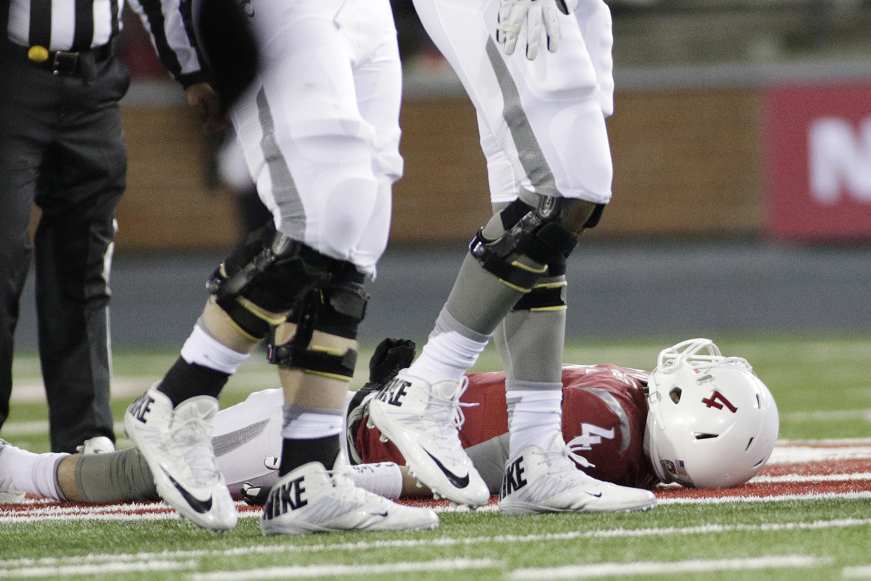 FILE - In this Nov. 21, 2015, file photo, Washington State quarterback Luke Falk (4), who was later carted off the filed, rests after being tackled during the second half of an NCAA college football game against Colorado, in Pullman, Wash. The Big 12 cham