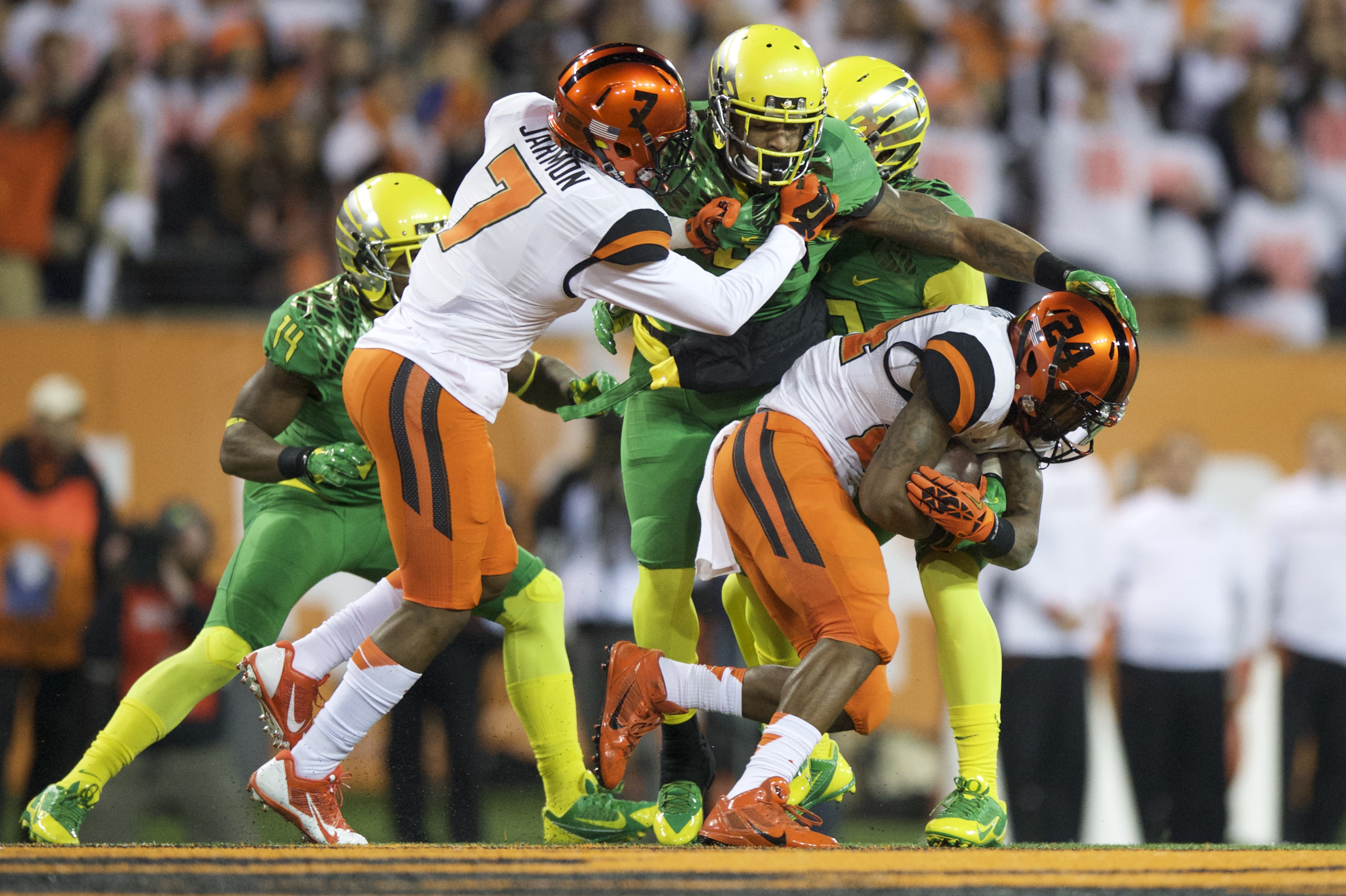FILE - In this Nov. 29, 2014, file photo, Oregon State running back Storm Woods (24) breaks away from Oregon defender Erick Dargan (4) with help from teammate Hunter Jarmon (7) during the first quarter of an NCAA college football game in Corvallis, Or. Wo