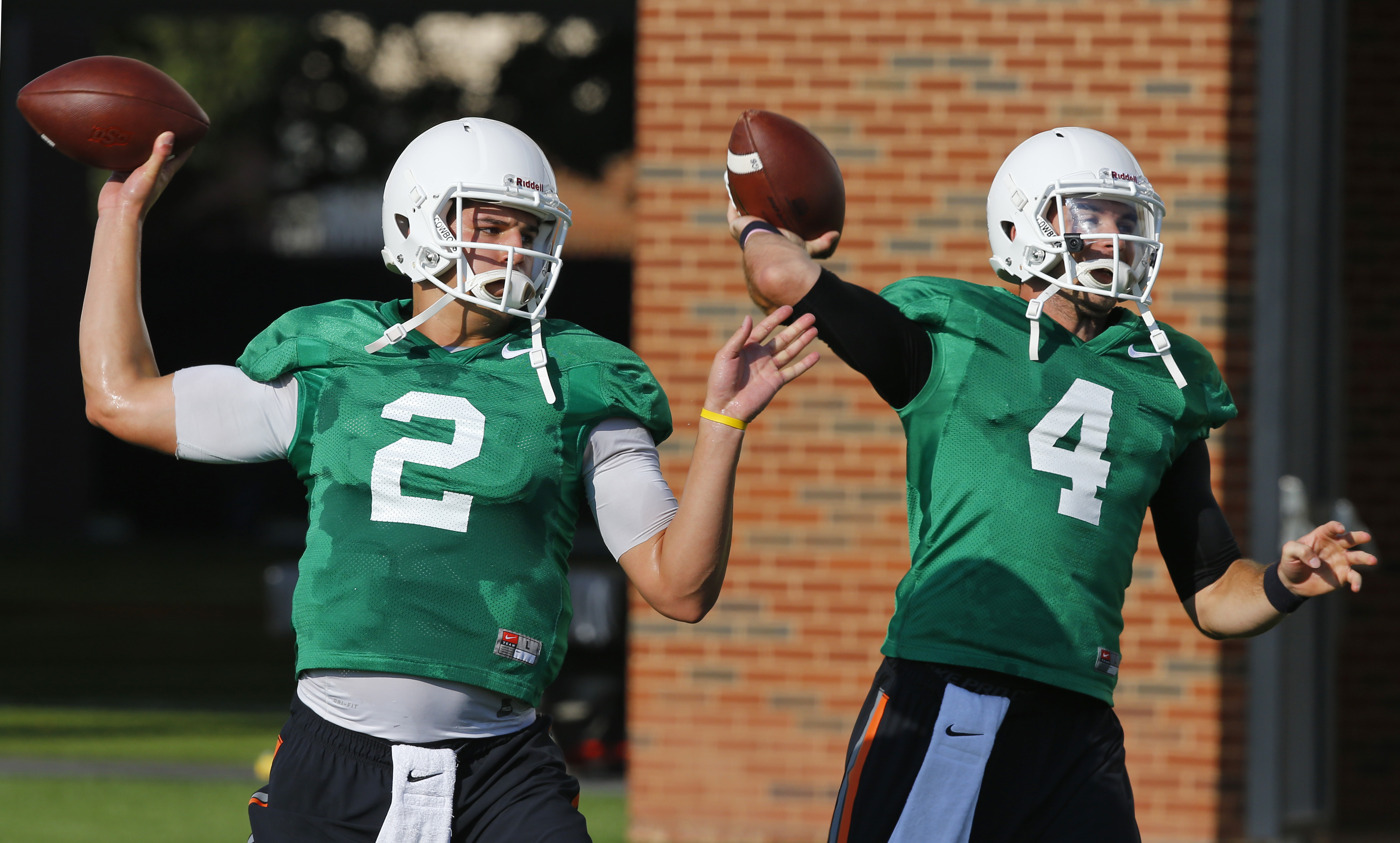 FILE - In this Aug. 6, 2015, file photo, Oklahoma State quarterbacks Mason Rudolph (2) and J.W. Walsh throw during NCAA college football practice in Stillwater, Okla. Rudolph has passed for 3,591 yards, with 21 touchdown passes and just eight interception