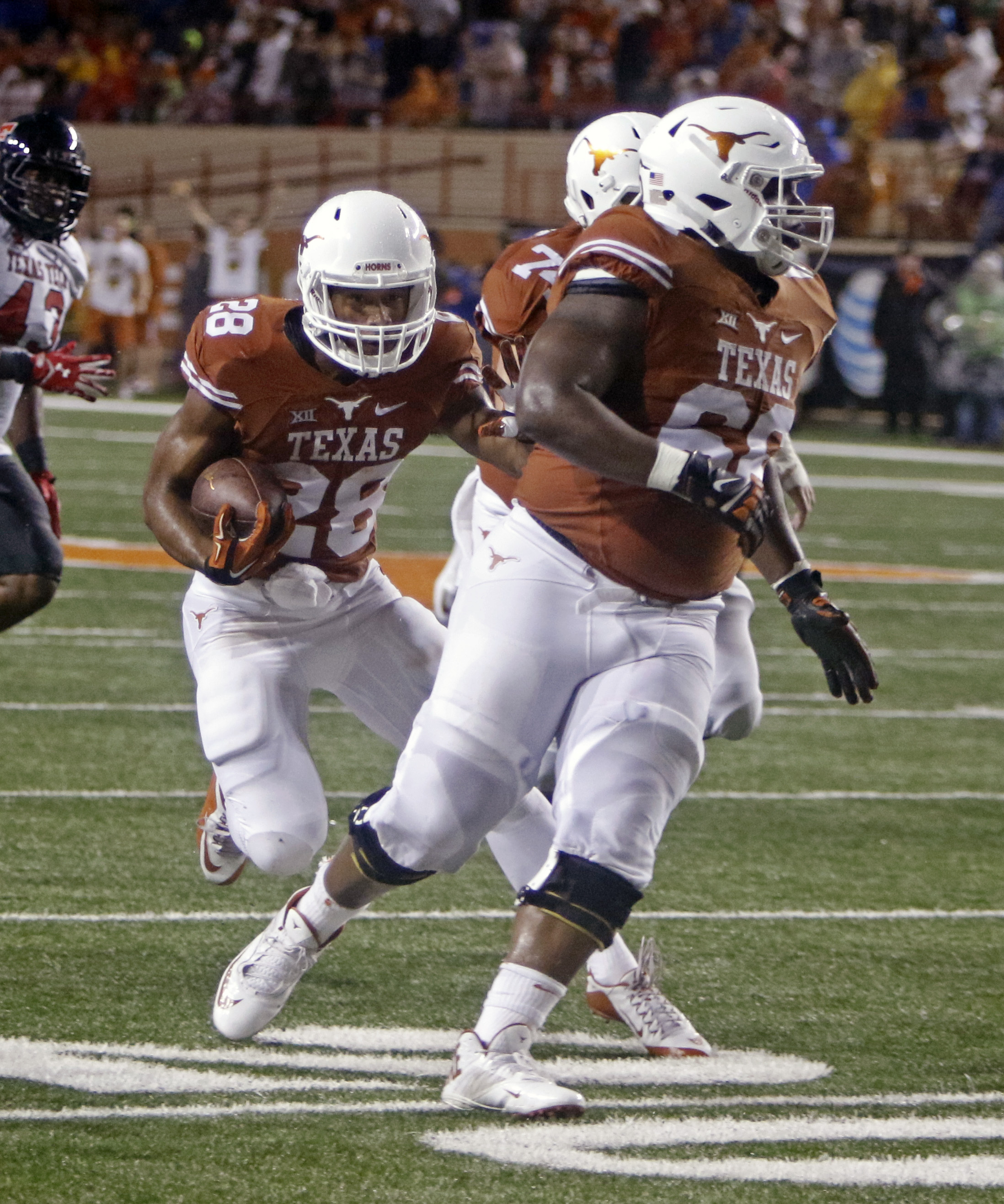 Texas running back Kirk Johnson (28) runs behind blockers Sedrick Flowers (66) and Taylor Doyle during the first half of an NCAA college football game against Texas Tech, Thursday, Nov. 26, 2015, in Austin, Texas. (AP Photo/Michael Thomas)