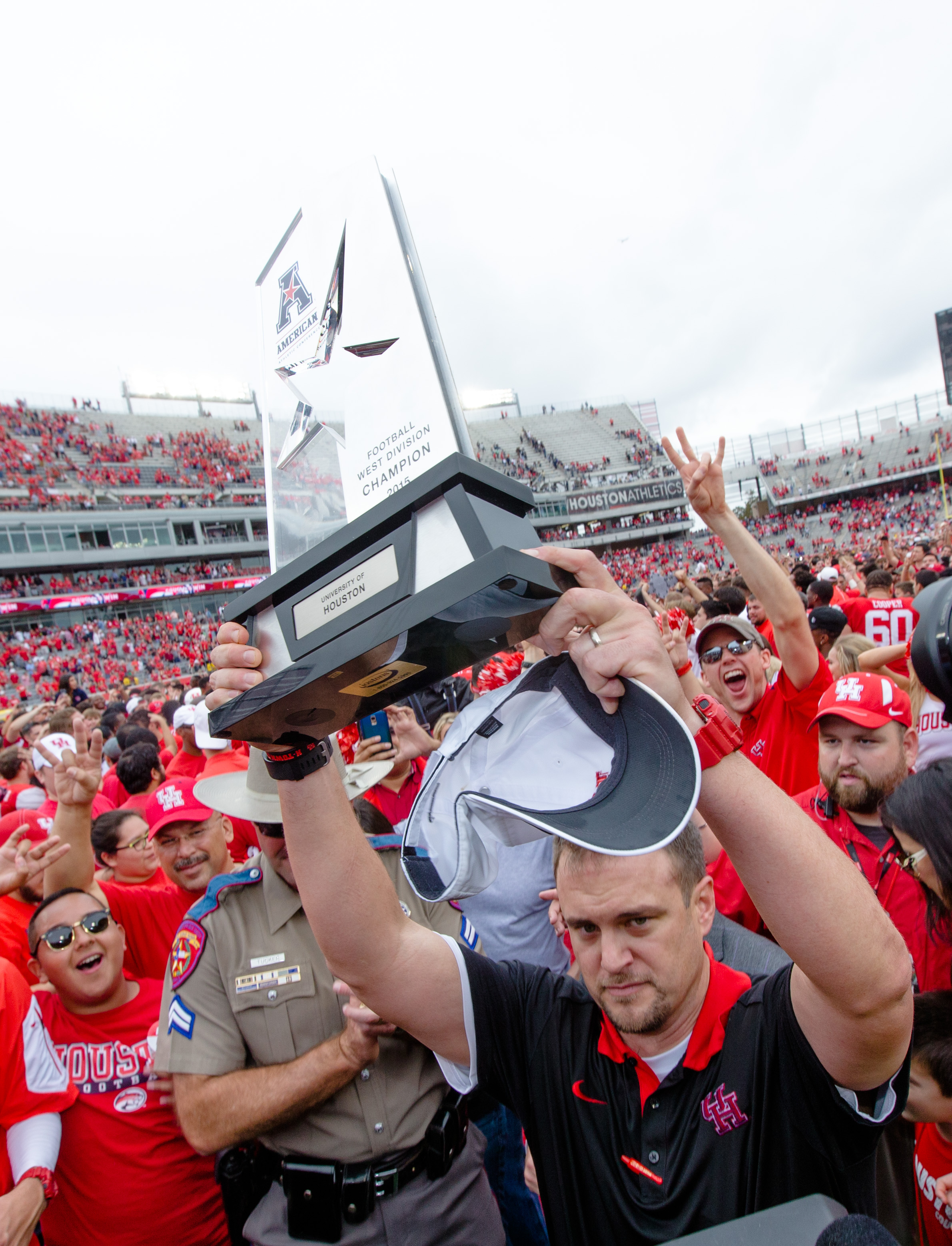 Houston's head coach Tom Herman holding the American West Trophy on the field after a NCAA college football game against Navy Friday, Nov. 27, 2015, in Houston, Texas. Houston defeated Navy 52-31.(AP Photo/Juan DeLeon)