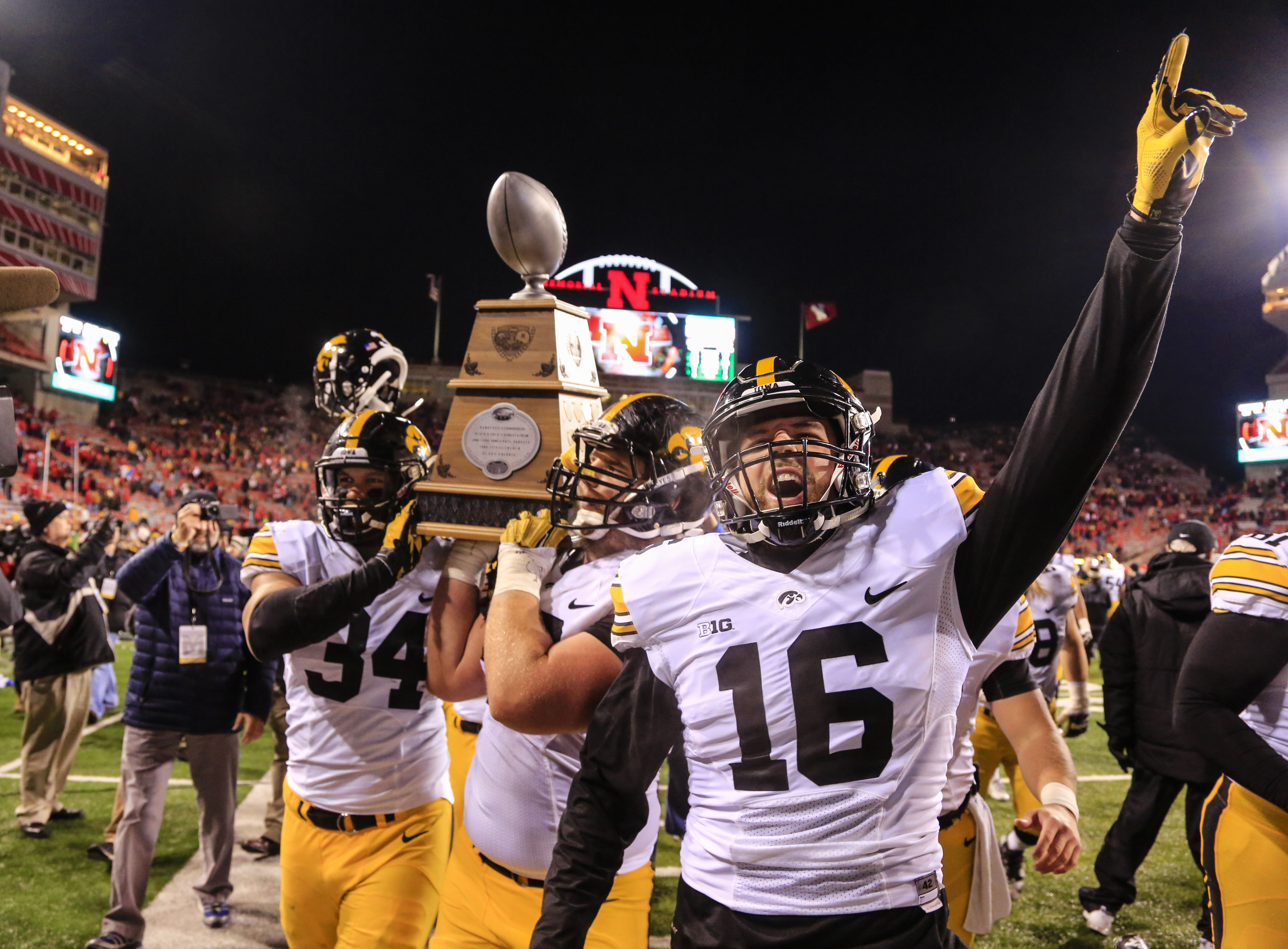 Iowa players, including Nate Meier (34) and Dillon Kidd (16), celebrate with the Heroes Trophy after defeating Nebraska 28-20 in an NCAA college football game in Lincoln, Neb., Friday, Nov. 27, 2015. (AP Photo/Nati Harnik)