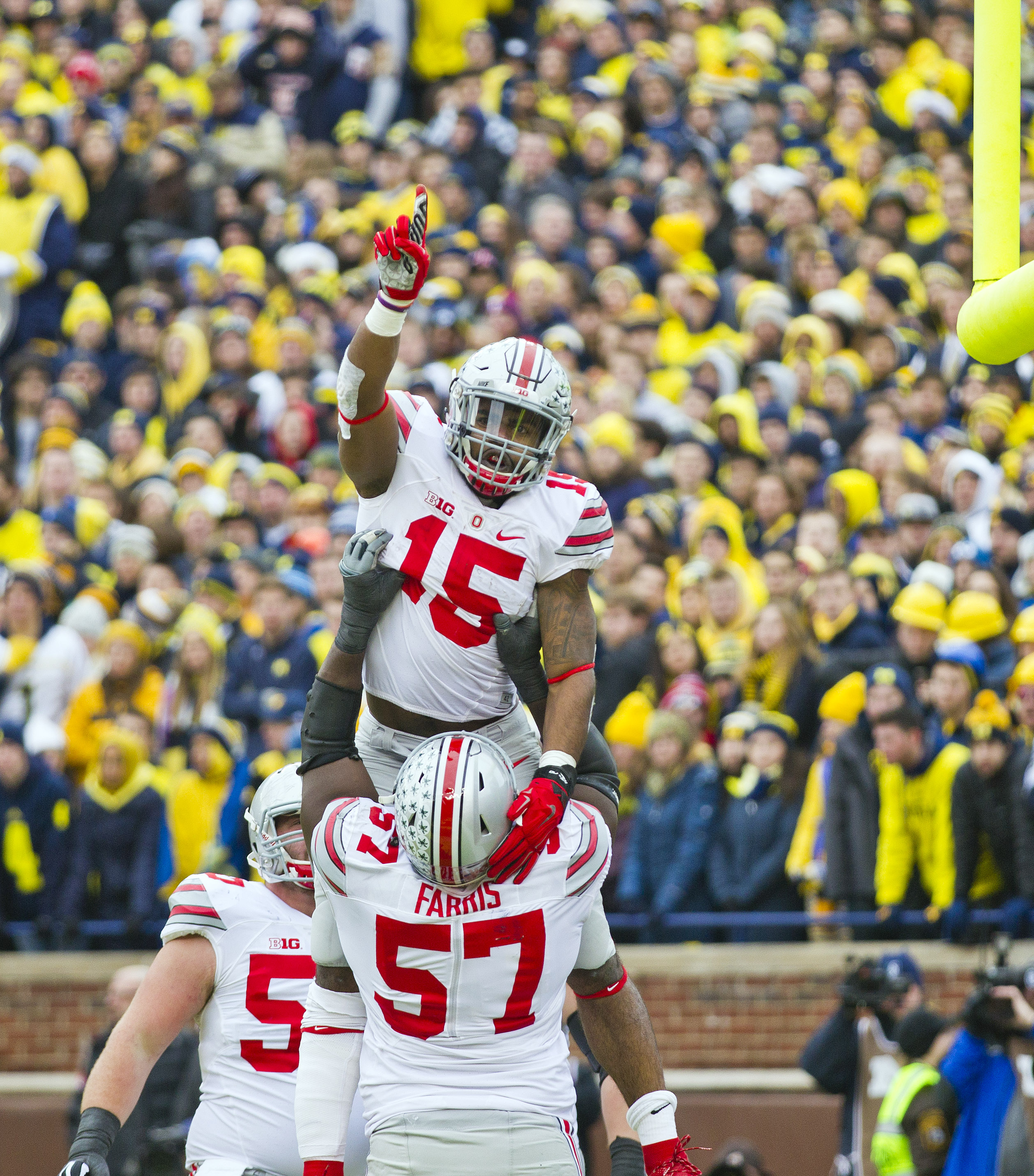 Ohio State running back Ezekiel Elliott (15) gets lifted in the air by offensive lineman Chase Farris (57) as they celebrate Elliott's touchdown in the second quarter of an NCAA college football game against Michigan in Ann Arbor, Mich., Saturday, Nov. 28