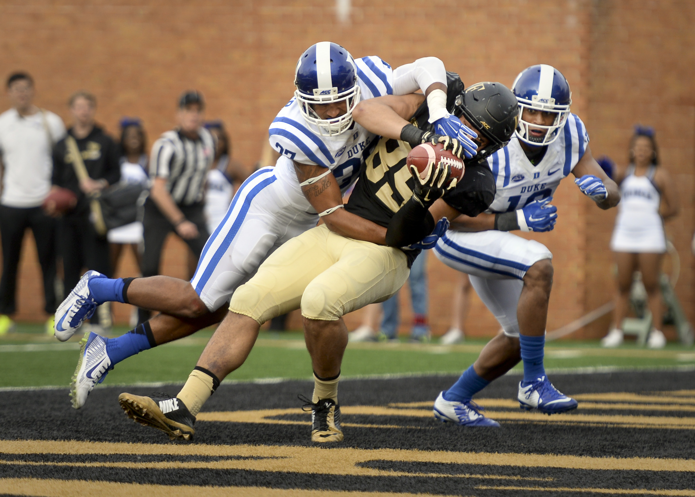 Wake Forest tight end Cam Serigne holds on to a touchdown pass as Duke's Phillip Carter, left, and Jeremy Cash, right, defend during during the second half of an NCAA college football game in Winston-Salem, N.C. Saturday, Nov. 28, 2015. (Lauren Carroll /T