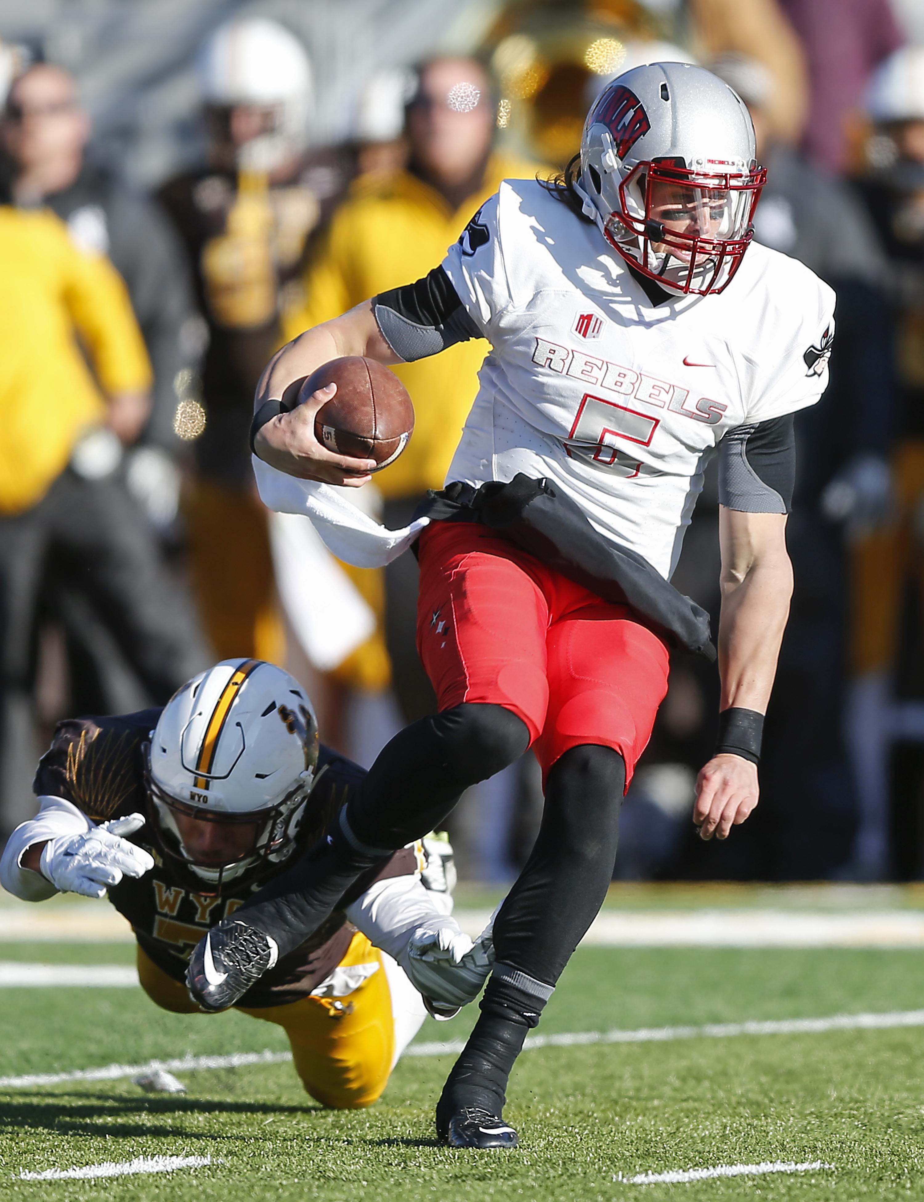 UNLV quarterback Blake Decker  runs past a Wyoming defender during the second quarter of an NCAA college football game, Saturday, Nov. 28, 2015, in Laramie, Wyo. (AP Photo/Michael Smith)