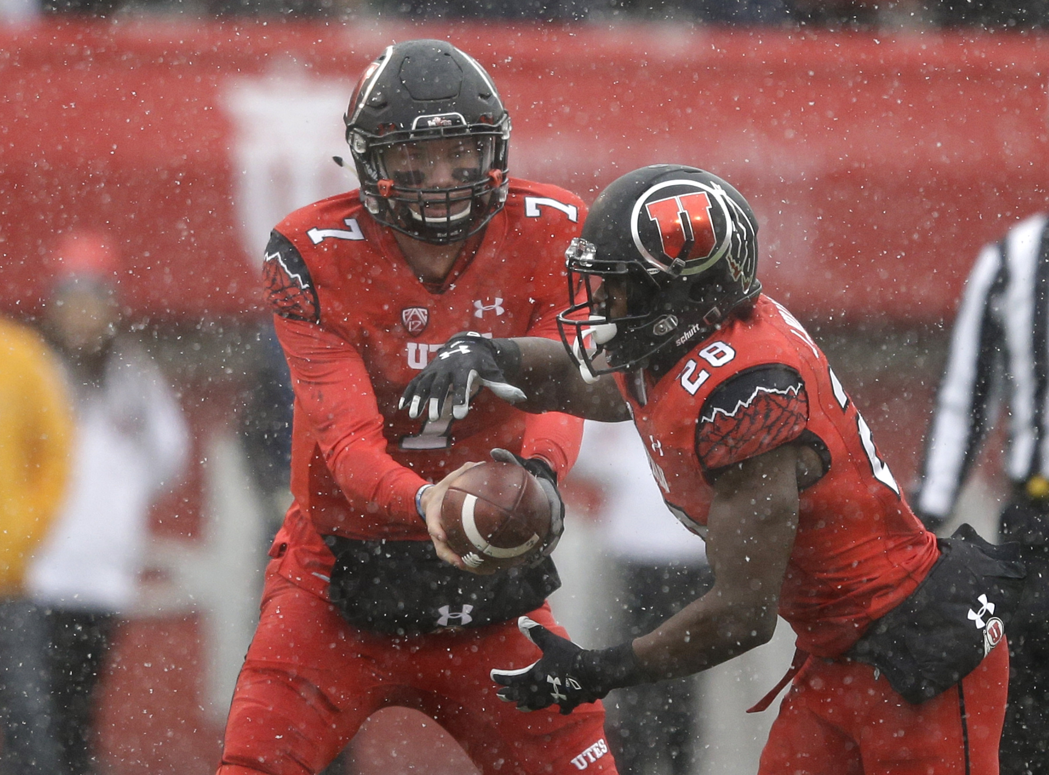 Utah quarterback Travis Wilson (7) hands the ball off to Utah running back Joe Williams (28) in the first half during an NCAA college football game against Colorado Saturday, Nov. 28, 2015, in Salt Lake City. (AP Photo/Rick Bowmer)