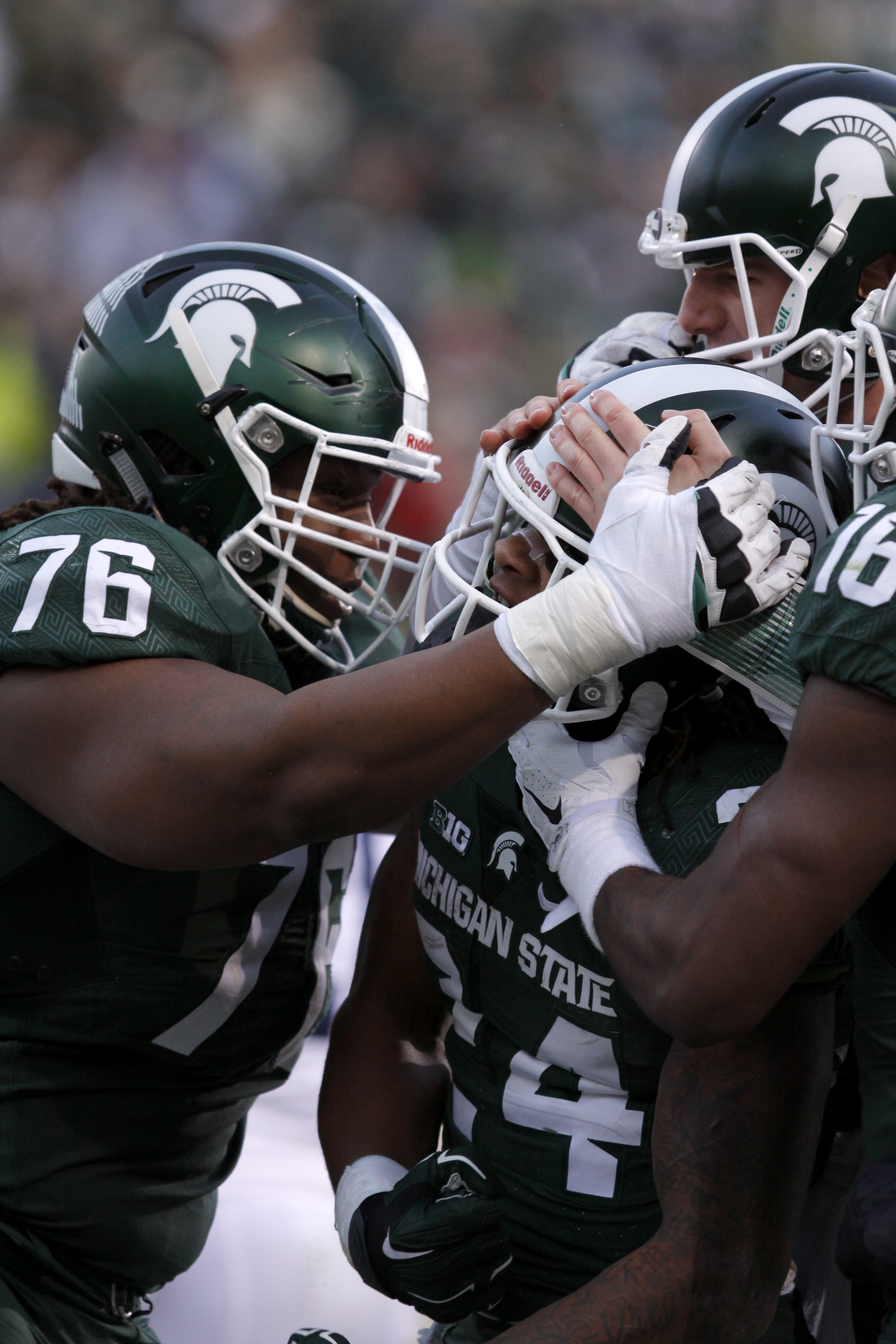Michigan State running back Gerald Holmes, center, offensive lineman Donavon Clark (76) and quarterback Connor Cook, right, celebrate Holmes' rushing touchdown against Penn State during the second quarter of an NCAA college football game, Saturday, Nov. 2