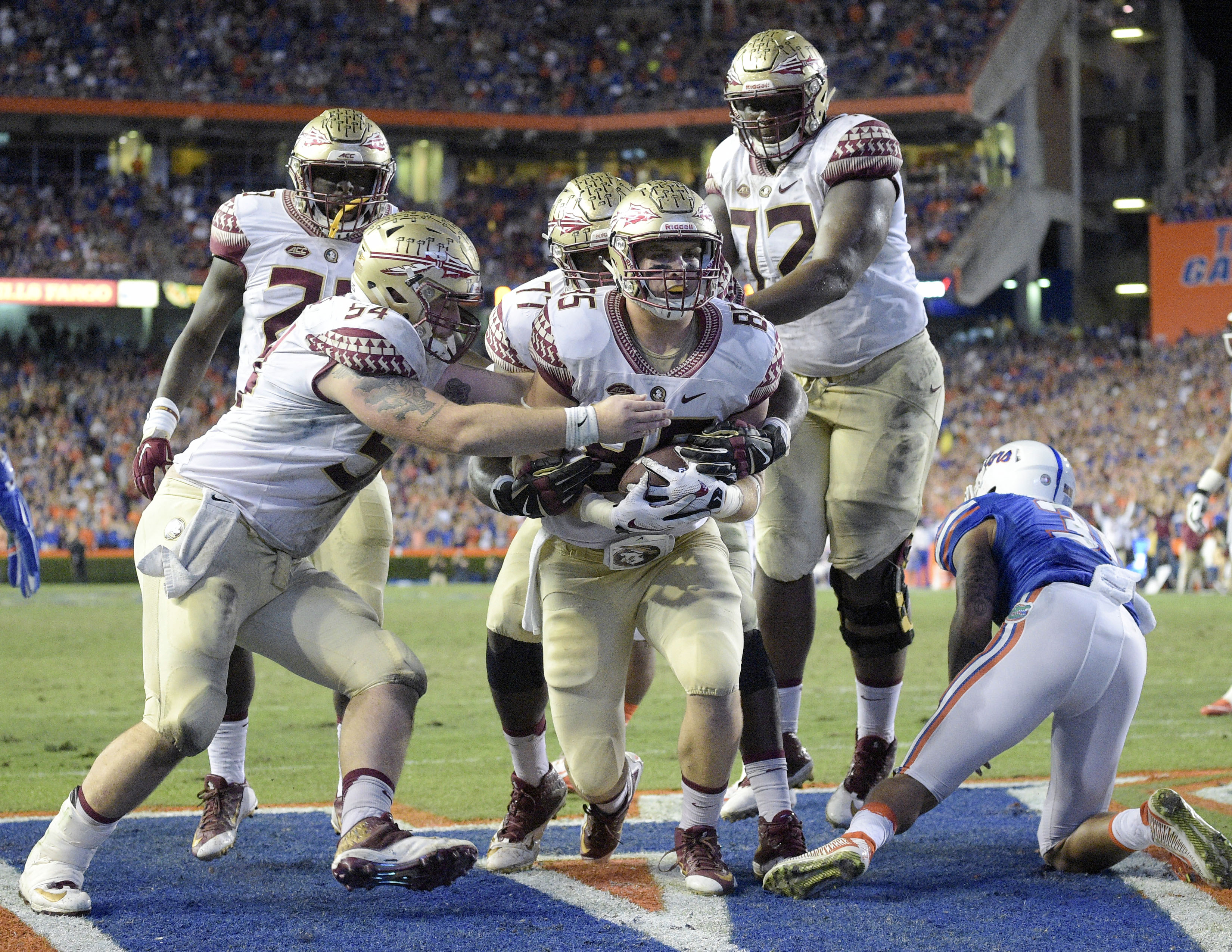 Florida State tight end Jeremy Kerr, center, celebrates with teammates after scoring a touchdown against Florida on a 1-yard pass play during the first half of an NCAA college football game, Saturday, Nov. 28, 2015, in Gainesville, Fla. (AP Photo/Phelan M