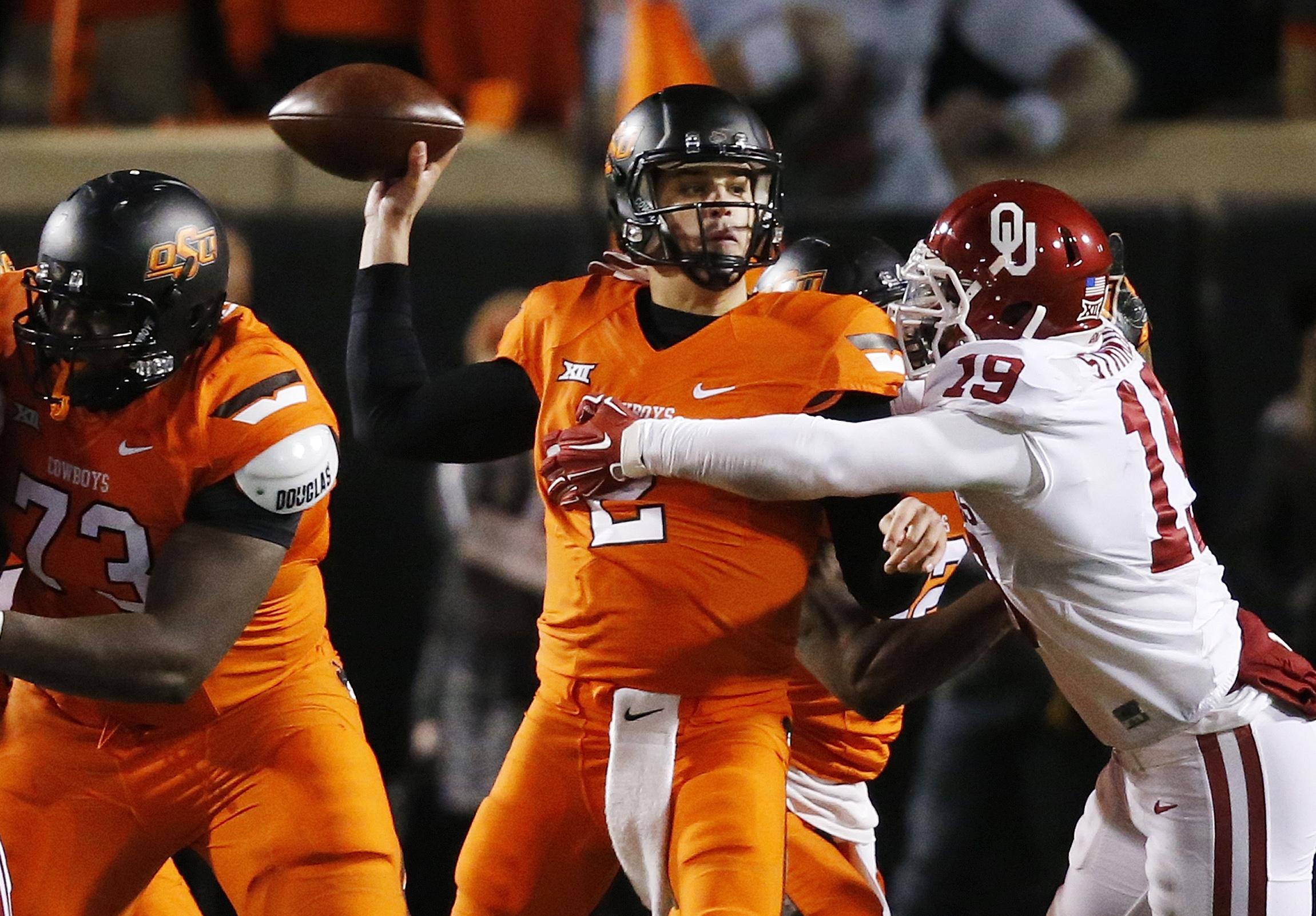 Oklahoma State quarterback Mason Rudolph (2) throws an interception under pressure from Oklahoma linebacker Eric Striker (19) in the second quarter of an NCAA college football game in Stillwater, Okla., Saturday, Nov. 28, 2015. (AP Photo/Sue Ogrocki)