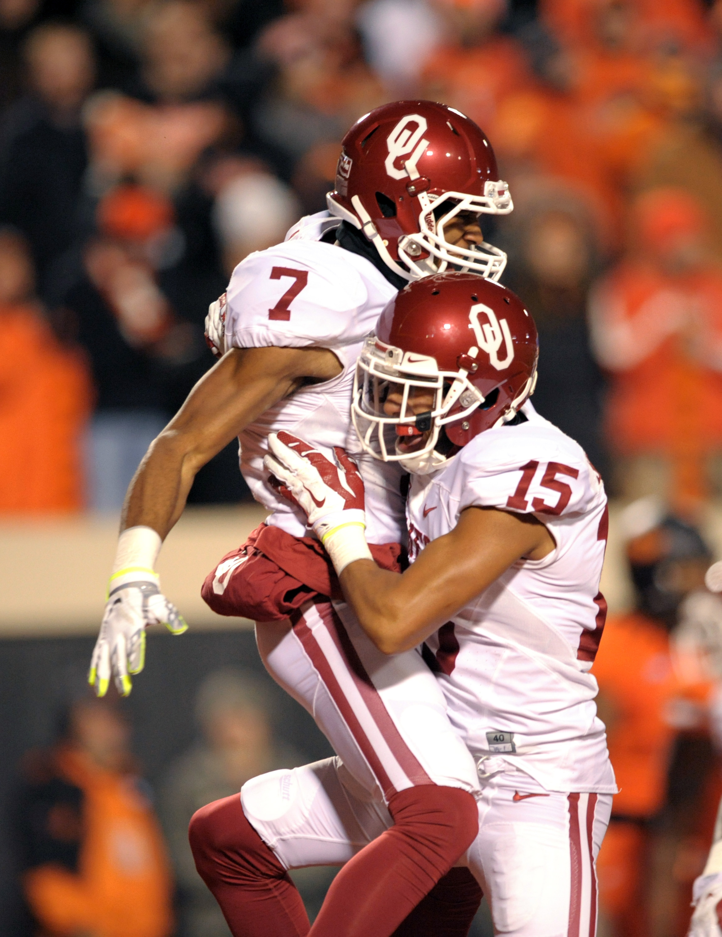 Oklahoma cornerback Jordan Thomas (7) celebrates his touchdown off an interception with corner back Zach Sanchez during an NCAA college football game against Oklahoma St in Stillwater, Okla., Saturday, Nov. 28, 2015. (AP Photo/Brody Schmidt)
