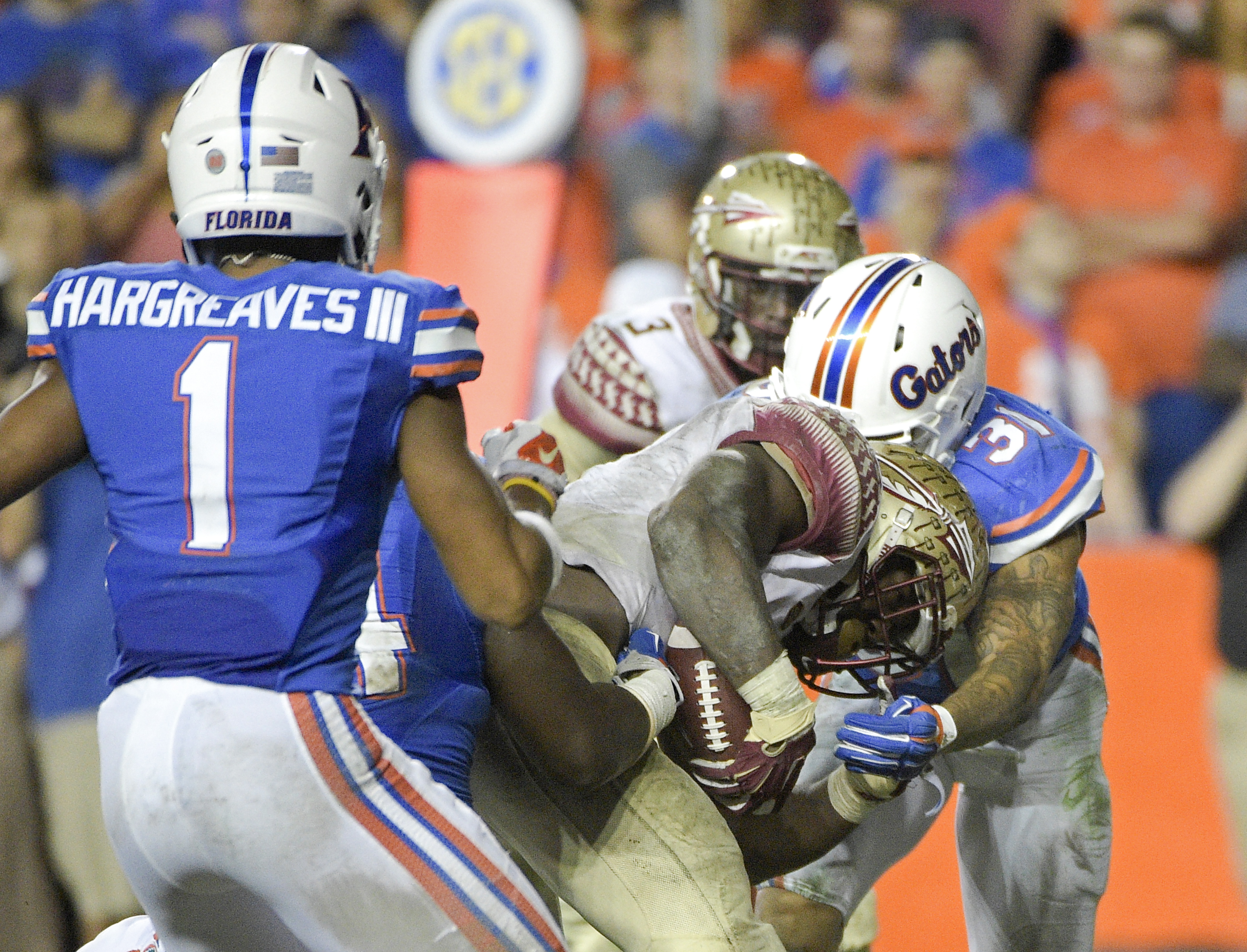 Florida State running back Dalvin Cook, center pushes past Florida defensive back Vernon Hargreaves III (1) and defensive back Jalen Tabor (31) for a touchdown during the second half of an NCAA college football game, Saturday, Nov. 28, 2015, in Gainesvill