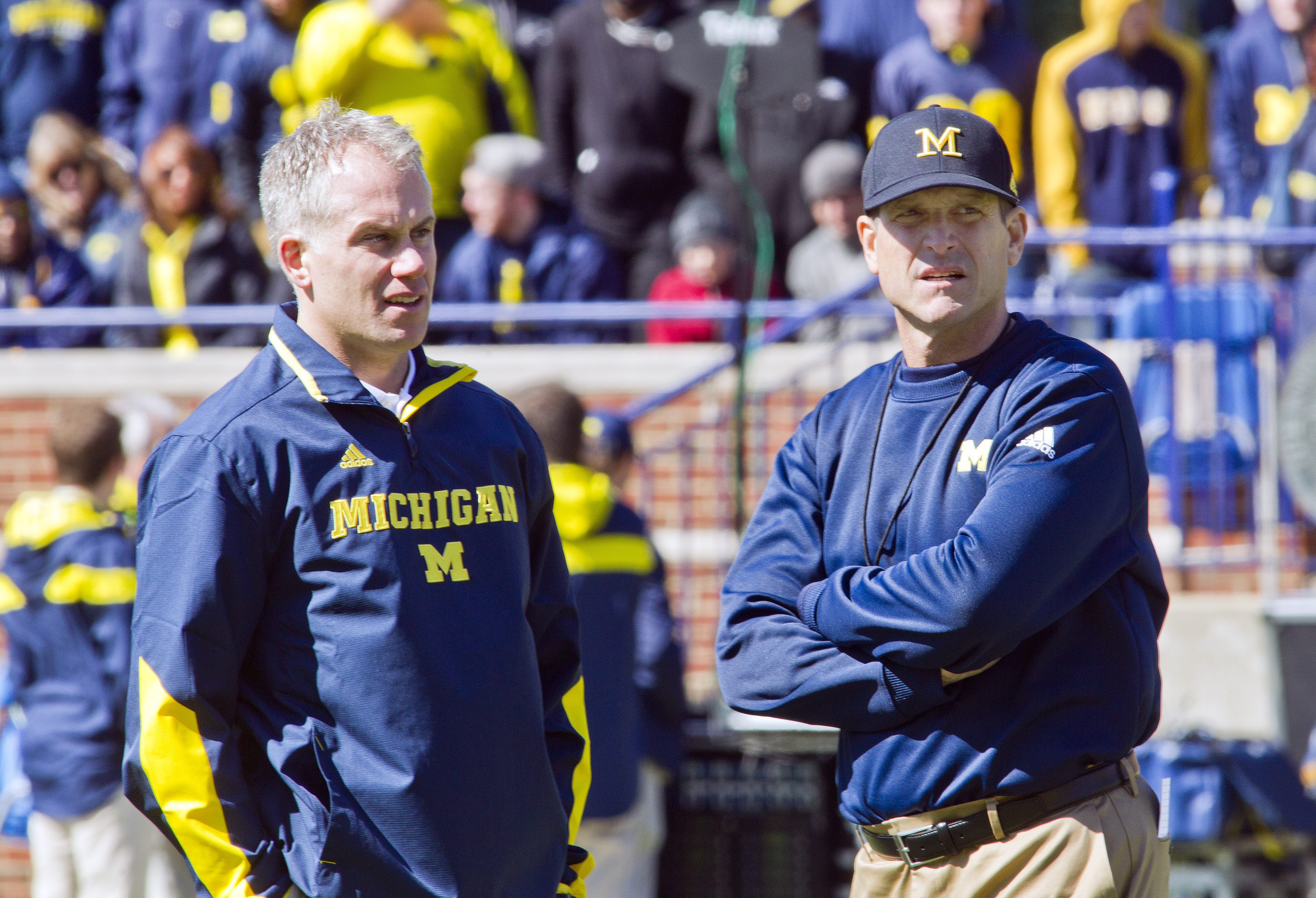 Michigan defensive coordinator D.J. Durkin, left, and head coach Jim Harbaugh, right, watch players warmup before the NCAA college football team's spring game in Ann Arbor, Mich., Saturday, April 4, 2015. (AP Photo/Tony Ding)