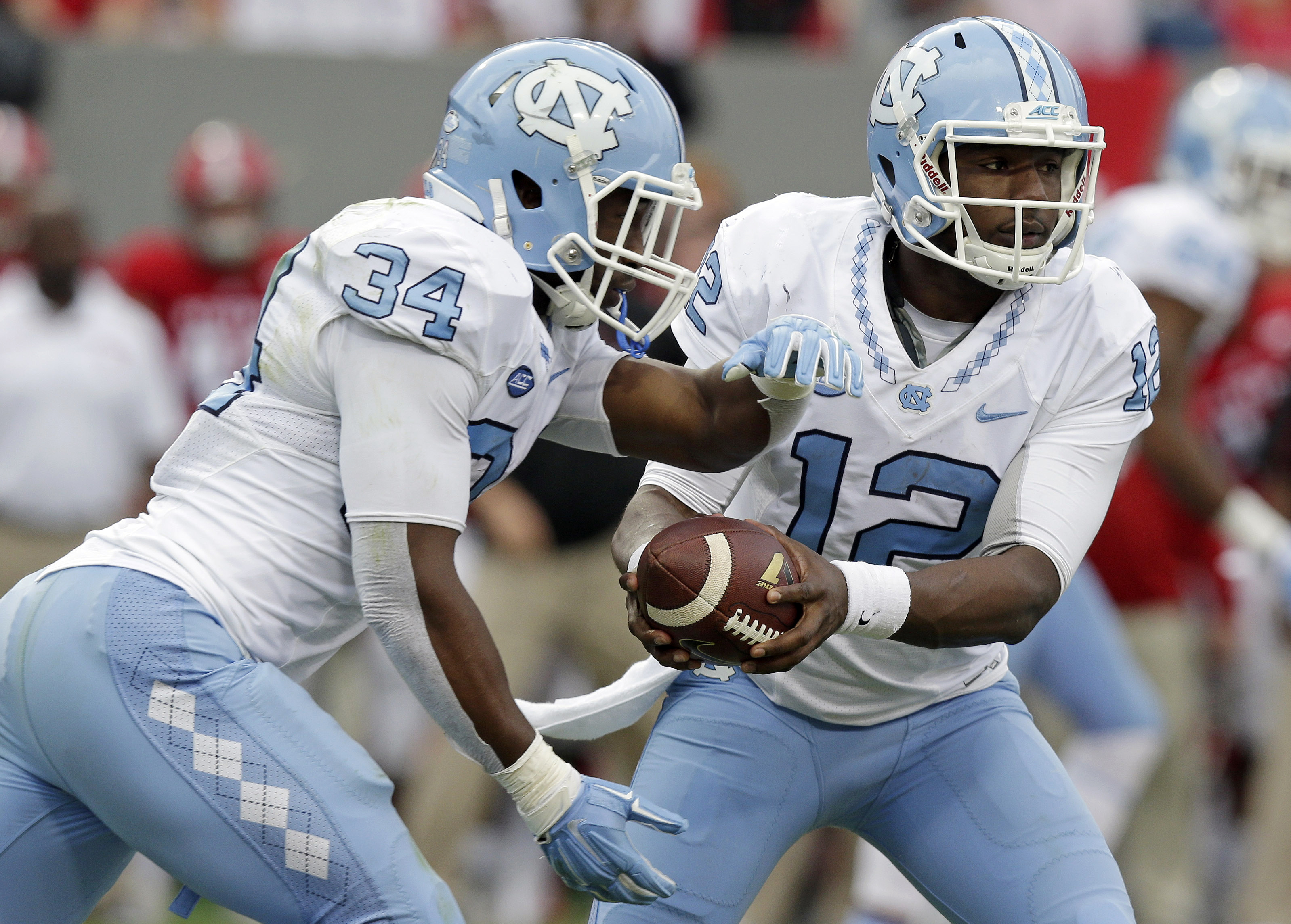 FILE - In this Nov. 28, 2015 file photo, North Carolina quarterback Marquise Williams (12) hands the ball off to Elijah Hood (34) during the first half an NCAA college football game against North Carolina State in Raleigh, N.C.  Eighth-ranked North Caroli
