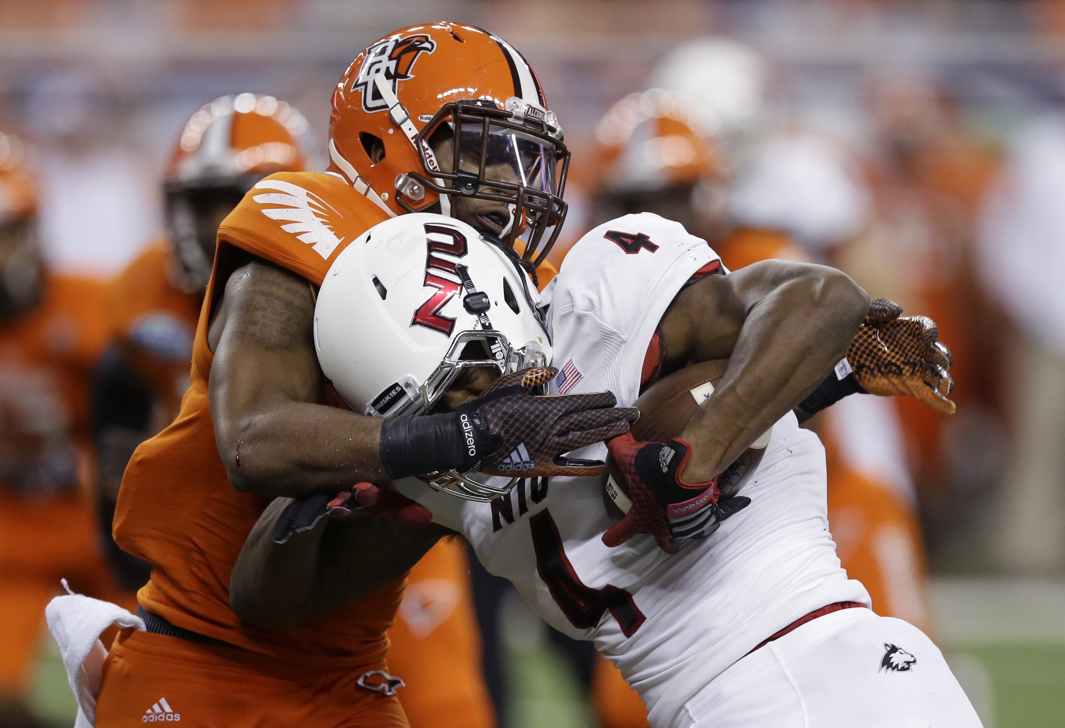 FILE - In this Dec. 5, 2014 file photo, Northern Illinois wide receiver Da'Ron Brown (4) is tackled by Bowling Green defensive back Brian Sutton (3) during the first half of the Mid-American Conference championship NCAA college football game in Detroit. B