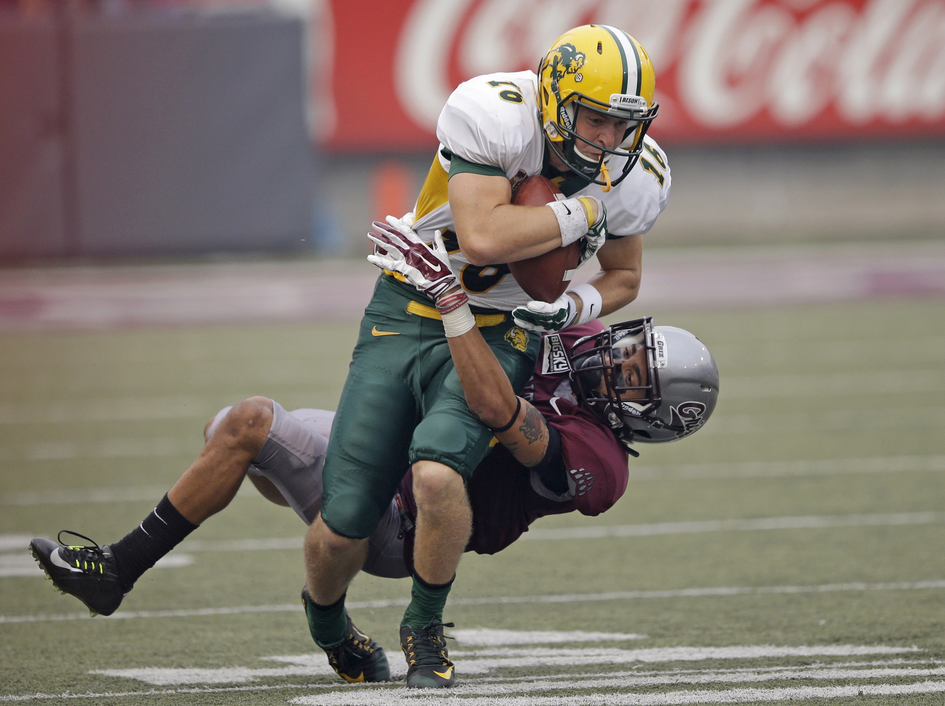 FILE - In this Aug. 29, 2015, file photo, North Dakota State wide receiver RJ Urzendowski (16) is tackled by Montana cornerback JR Nelson (18) during an NCAA college football game in Missoula, Mont. Montana rallied to win the game 38-35 on the final play