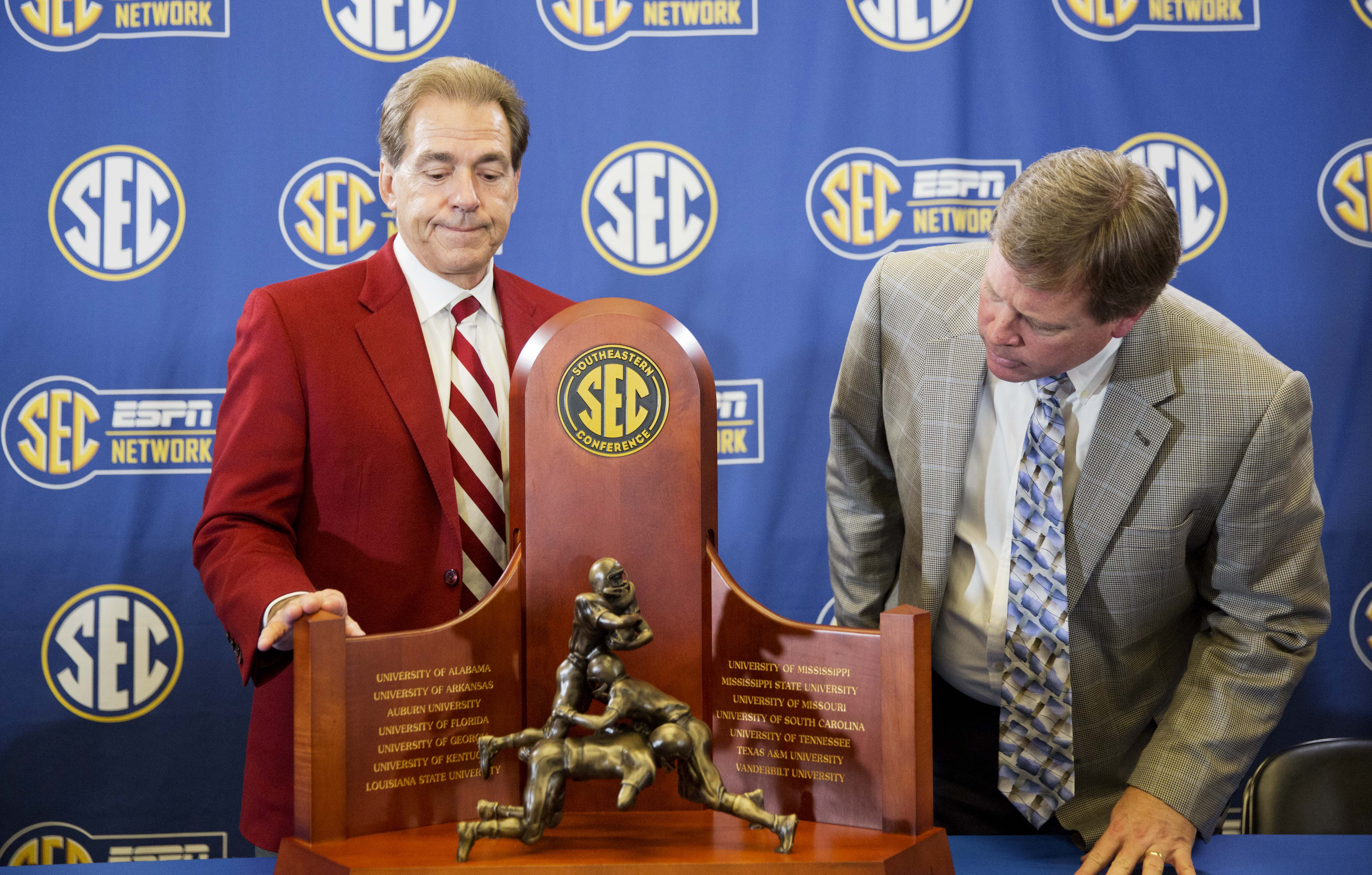Alabama head coach Nick Saban, left, and Florida head coach Jim McElwain look down at the trophy during a press conference held ahead of Saturday's Southeastern Conference championship NCAA college football game, Friday, Dec. 4, 2015, in Atlanta. (AP Phot