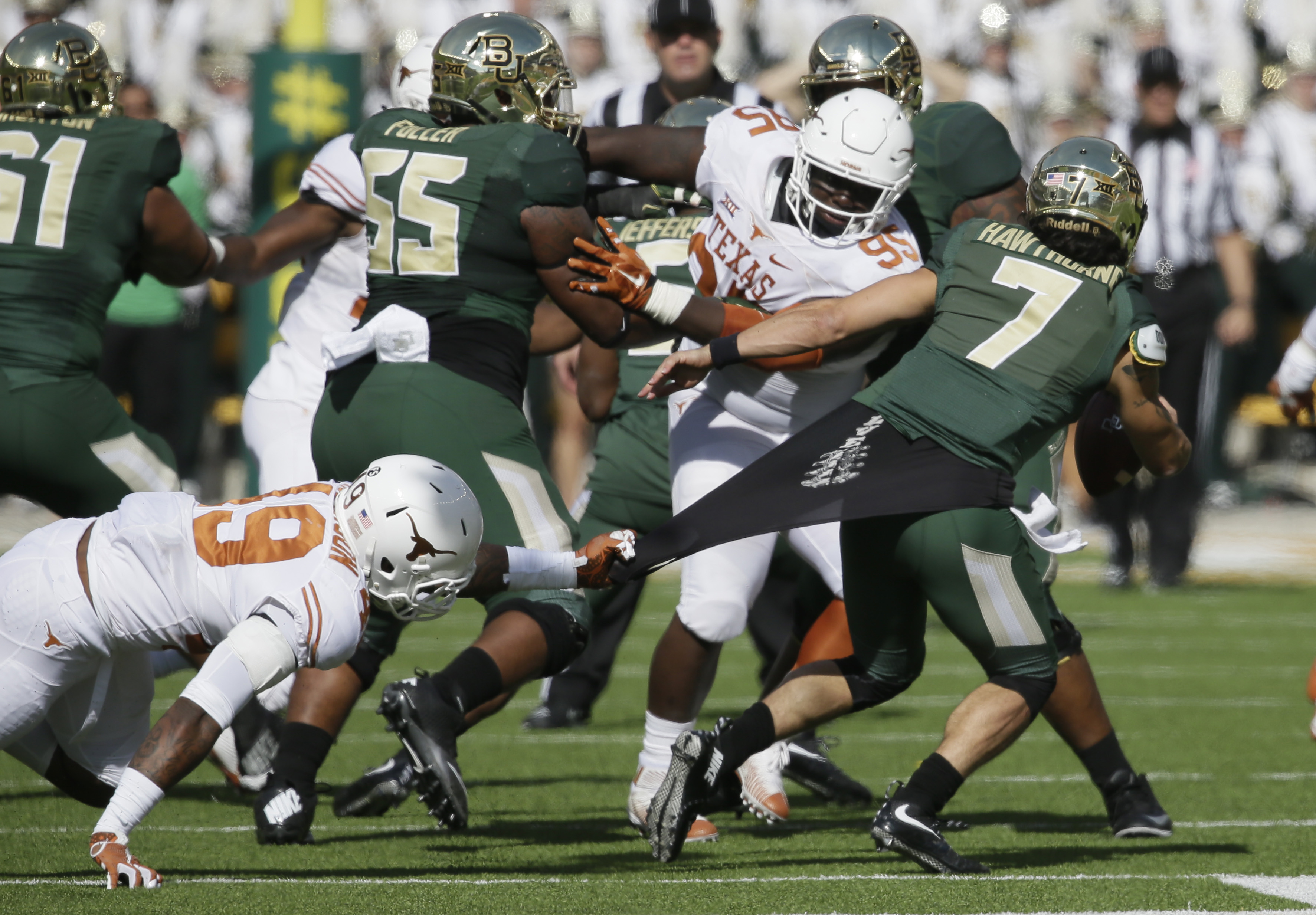 Baylor quarterback Lynx Hawthorne (7) is pulled by Texas defensive end Derick Roberson (49) as Baylor offensive lineman Kyle Fuller (55) blocks Texas defensive tackle Poona Ford (95) during the first half of an NCAA college football game Saturday, Dec. 5,