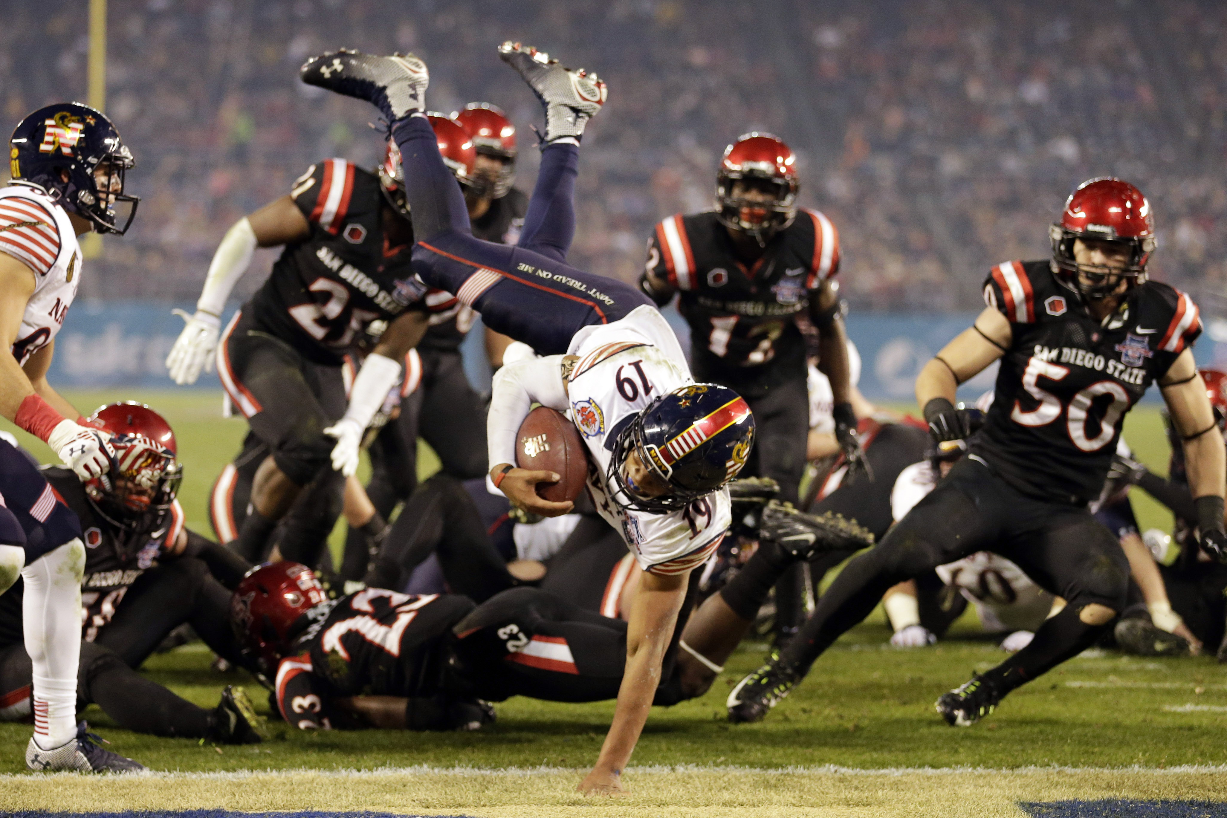 FILE - In this Dec. 23, 2014, file photo, Navy quarterback Keenan Reynolds (19) jumps into the end zone for a touchdown against San Diego State during the second half of the Poinsettia Bowl NCAA college football game, in San Diego. There are 41 bowl games