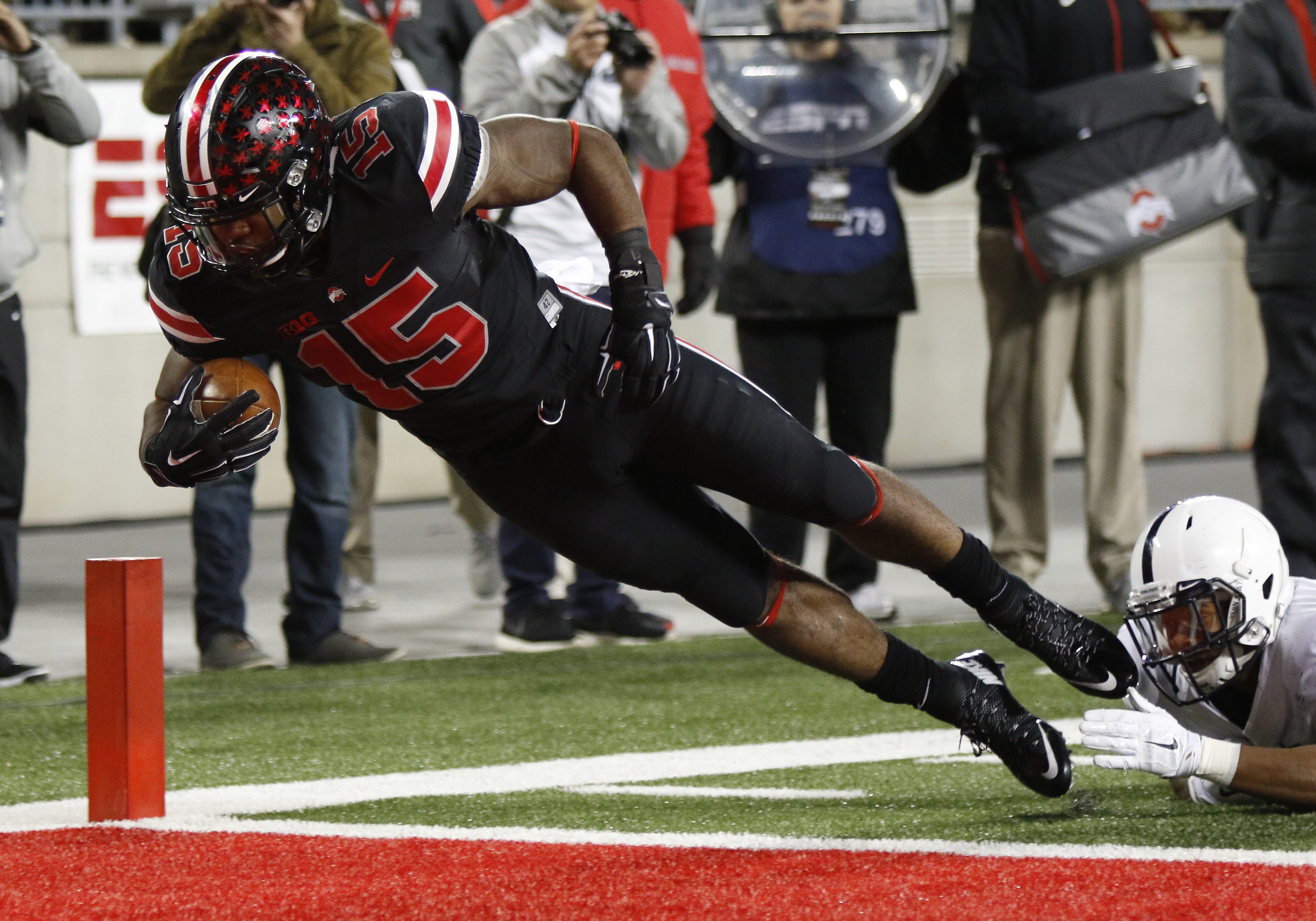 FILE - In this Oct. 17, 2015, file photo, Ohio State running back Ezekiel Elliott (15) escapes the grasp of Penn State defender Marcus Allen to score a touchdown during the first half of an NCAA college football game, in Columbus, Ohio. Offensive player o