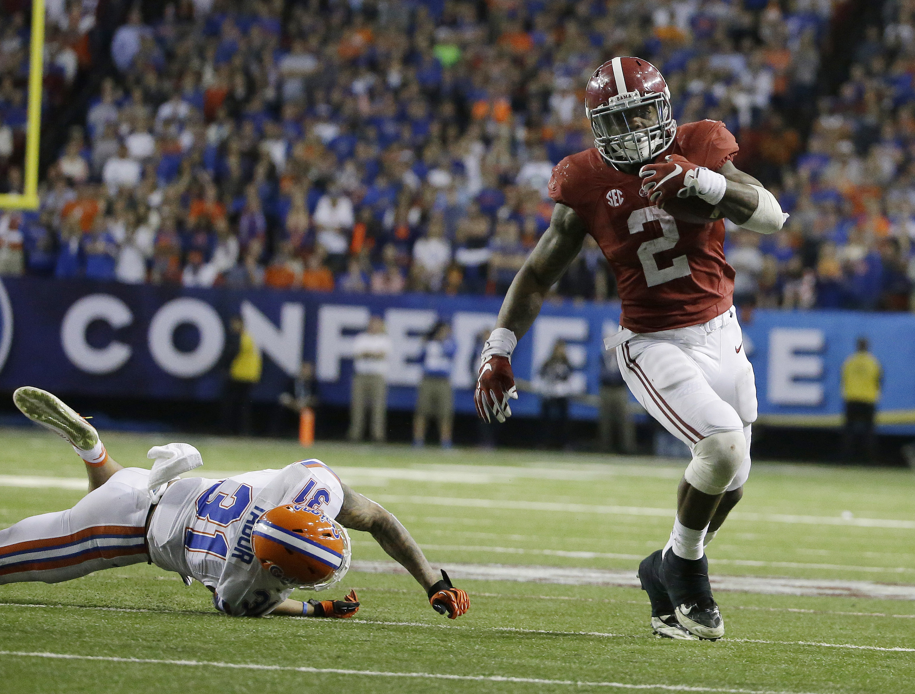 FILE - In this Dec. 15, 2015, file photo, Alabama running back Derrick Henry (2) runs by Florida defensive back Jalen Tabor (31) during the second half of the Southeastern Conference championship NCAA college football game, in Atlanta.  College football w