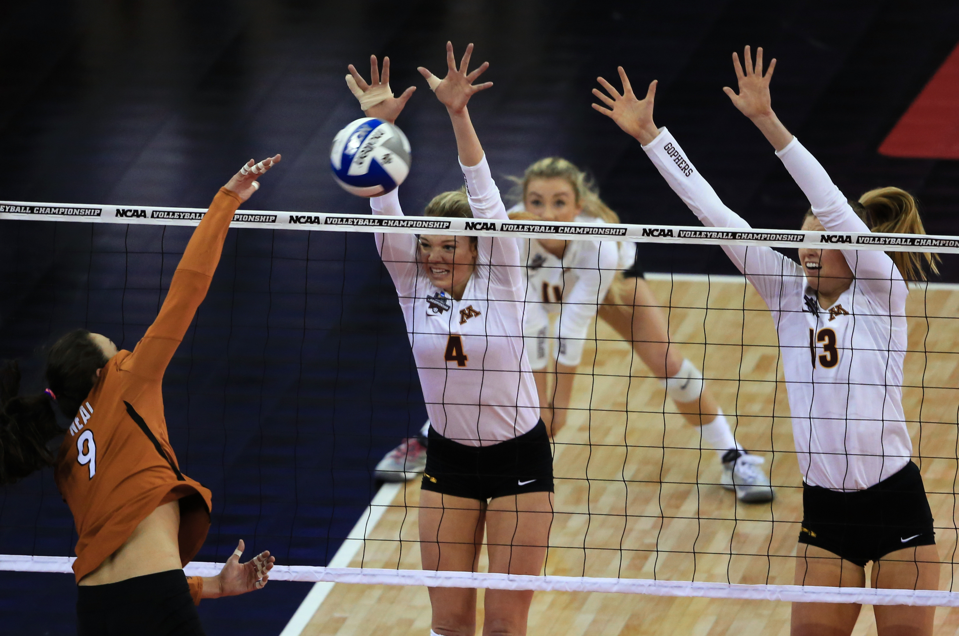 Texas' Amy Neal (9) h8ts a kill against Minnesota's Paige Tapp (4) and Molly Lohman (13) during an NCAA women's volleyball tournament semifinal in Omaha, Neb., Thursday, Dec. 17, 2015. (AP Photo/Nati Harnik)