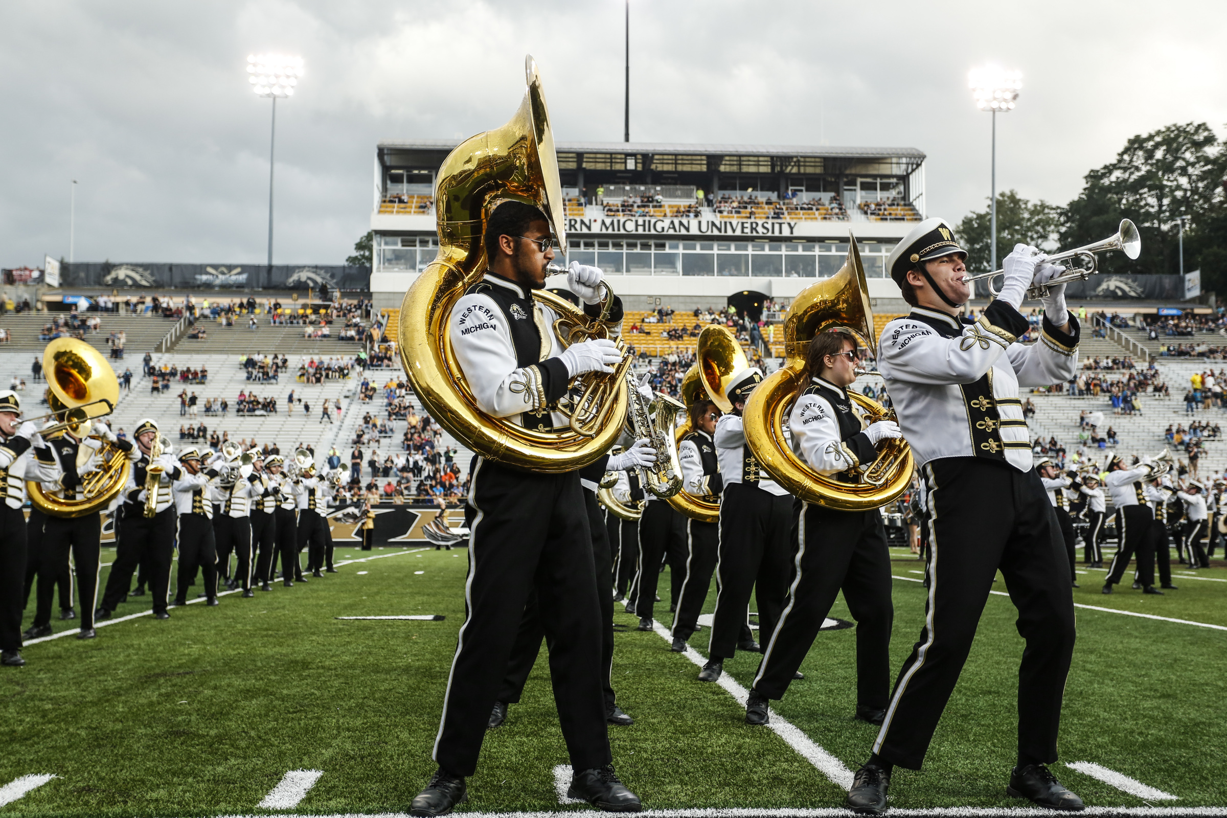 FILE -- In this Sept. 20, 2014, file photo, the Western Michigan marching band performs before an NCAA college football game in Kalamazoo, Mich. Marching bands and cheerleading squads are so much a part of college football's pageantry that many bowls stro